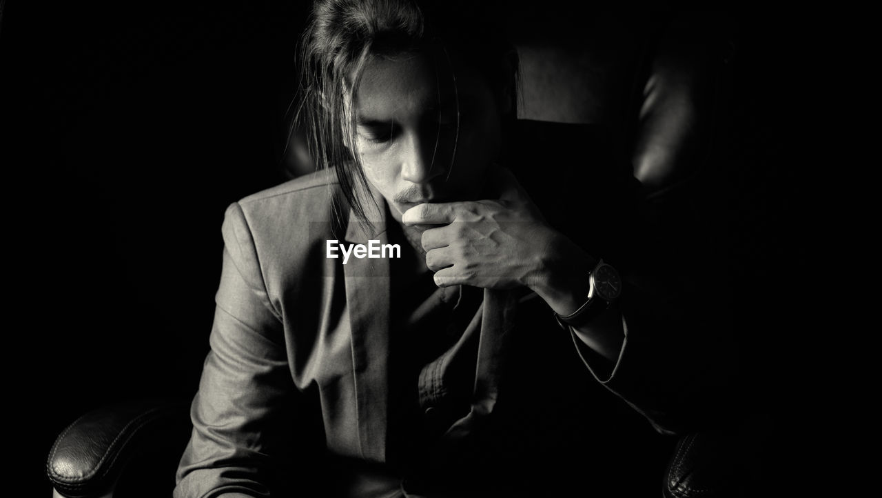 A long haired young business man wearing a suit thinking on revolving chair in darkness.