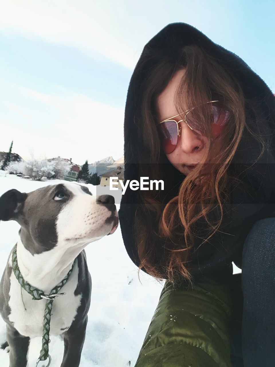 Portrait Of Woman With Dog Sitting Against Sky During Winter