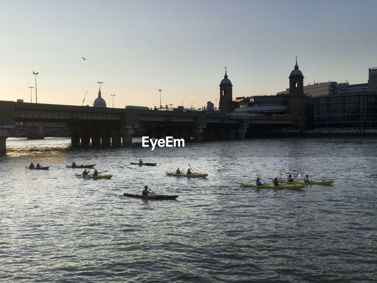People Rowing On River Against Sky In City During Sunset