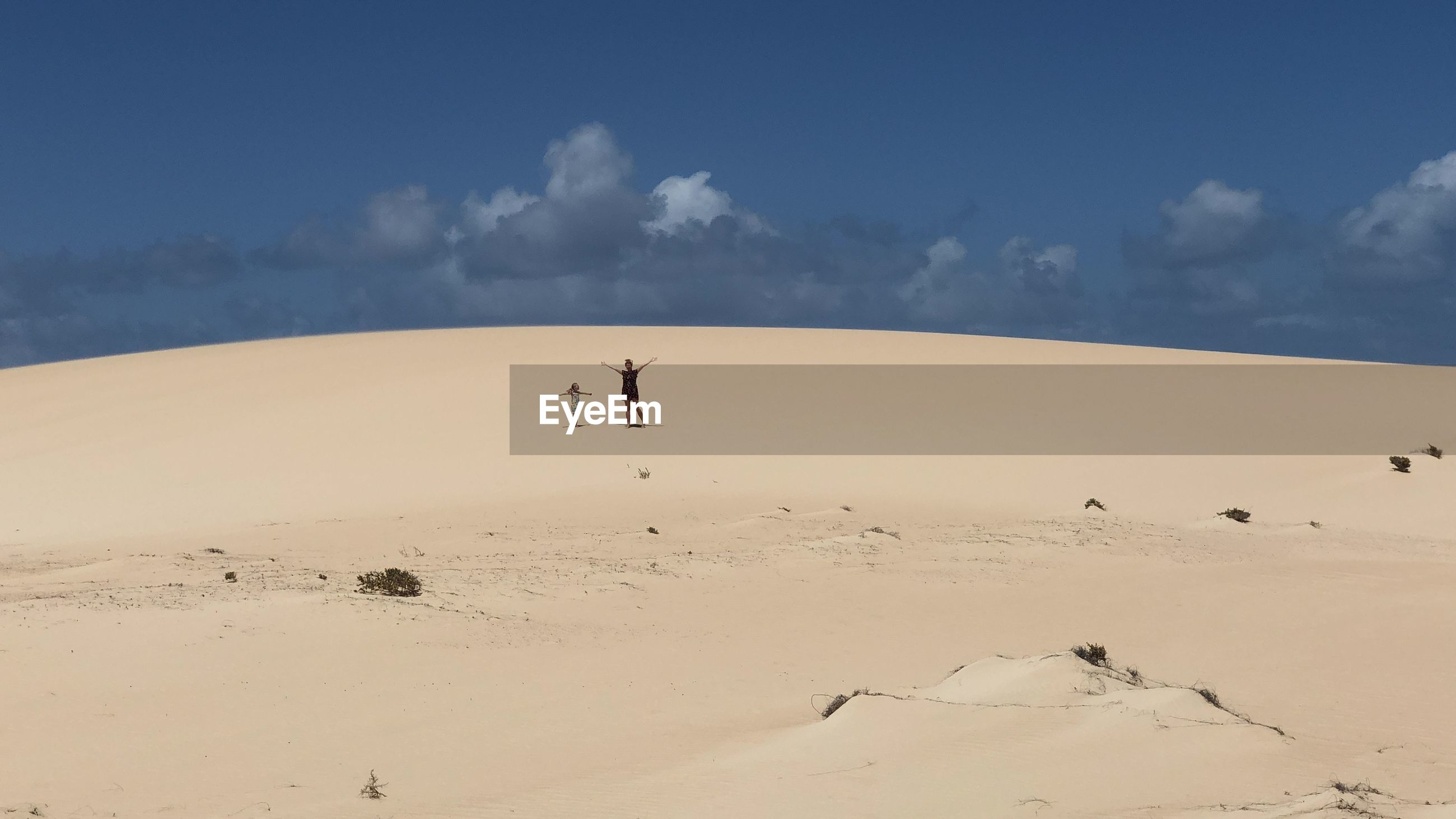 LOW ANGLE VIEW OF MAN STANDING ON DESERT LAND