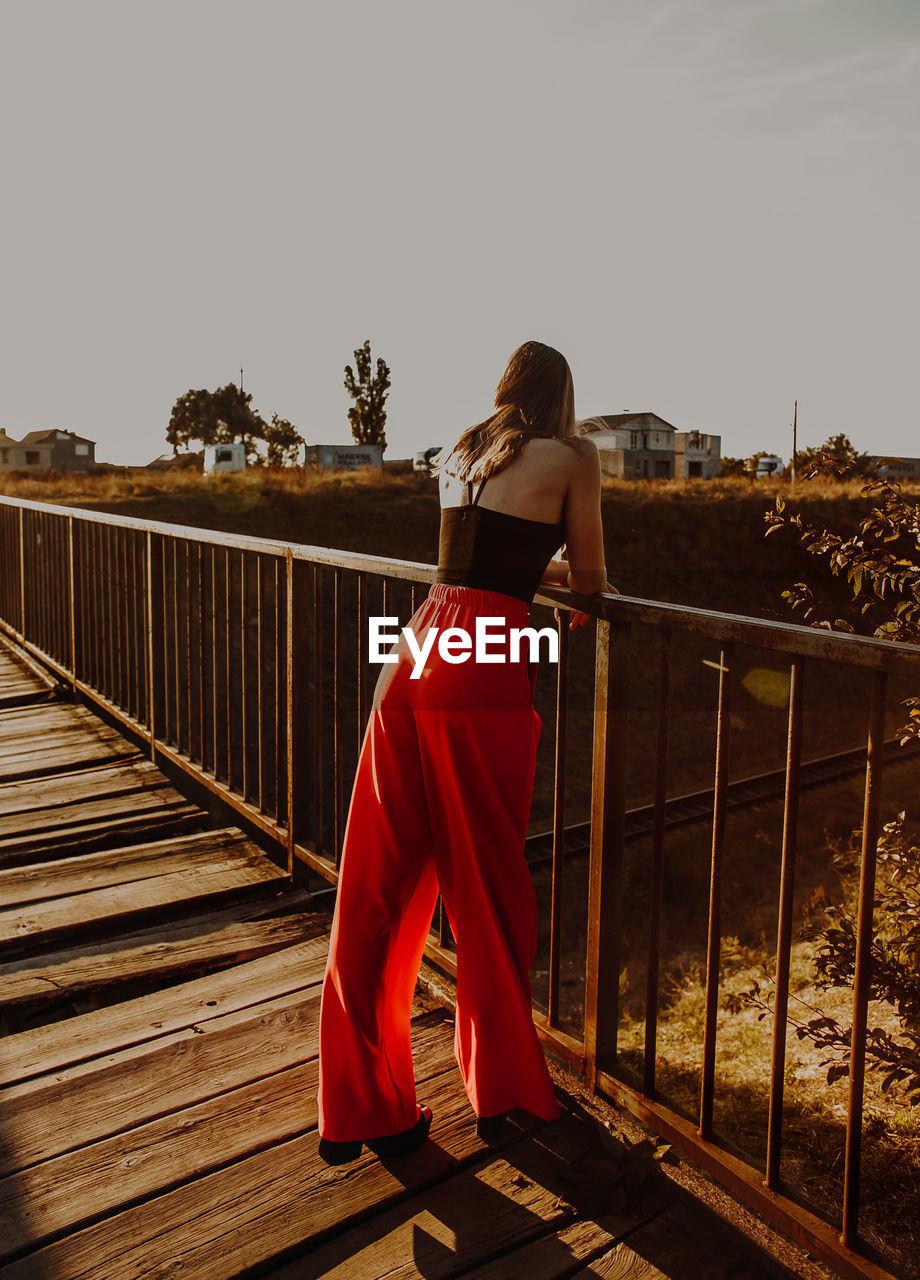 Full Length Of Woman Standing On Footbridge Against Clear Sky