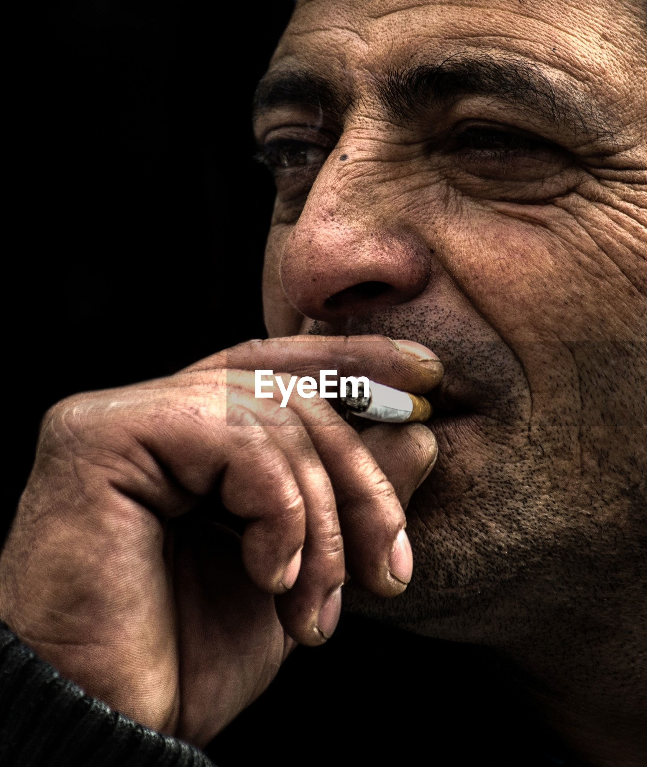 one person, men, indoors, black background, adult, studio shot, tobacco product, close-up, looking away, smoking issues, portrait, social issues, males, mid adult, headshot, cigarette, communication, mature men