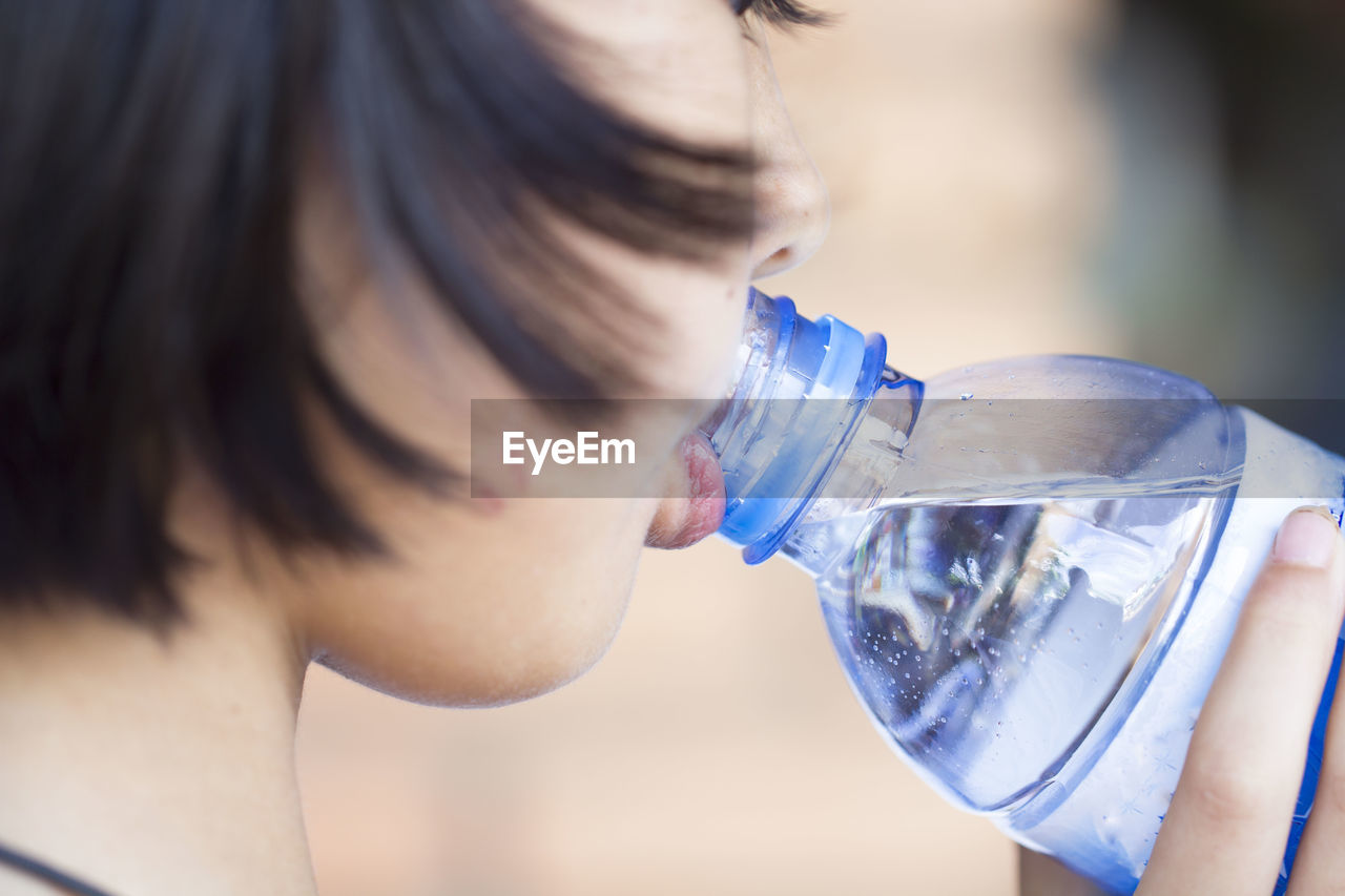 Close-Up Of A Woman Drinking From Water Bottle