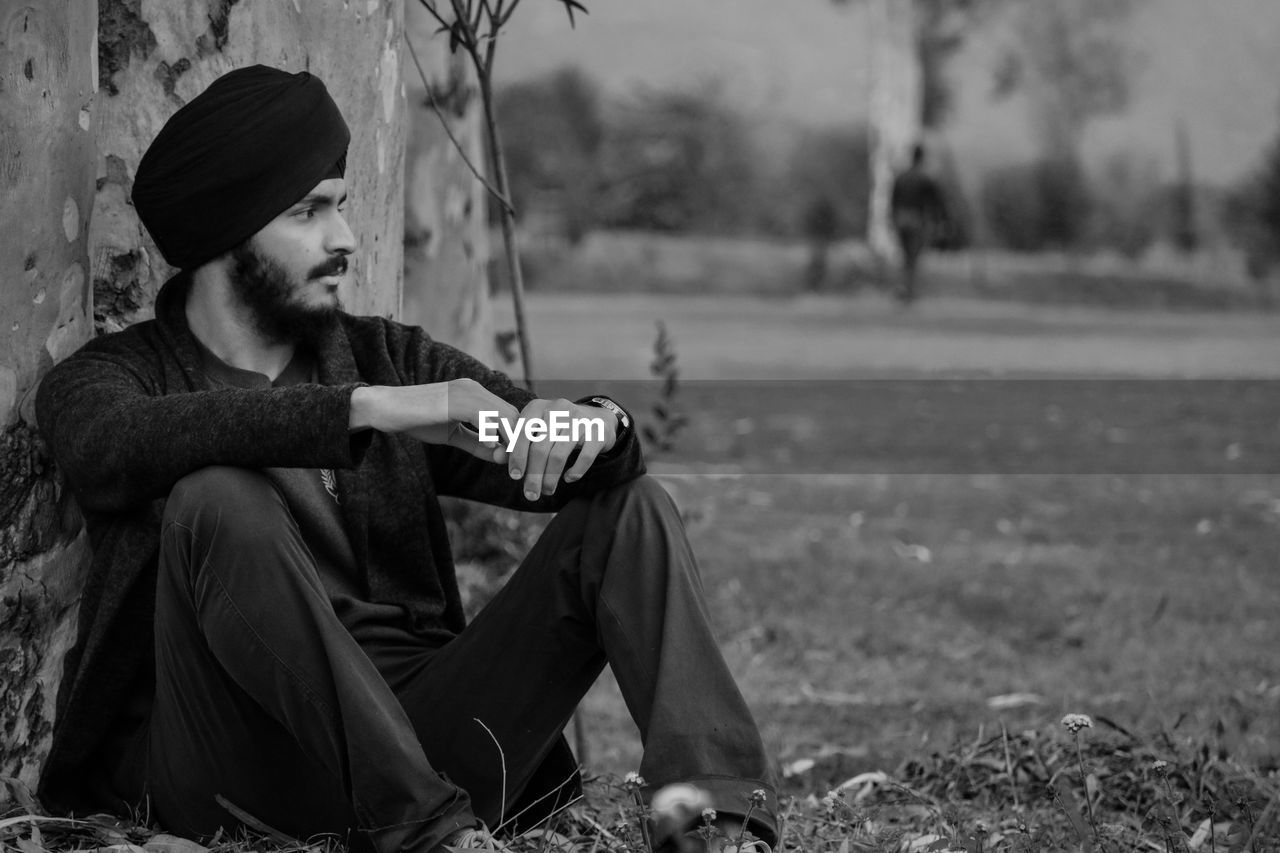 Young man looking away while sitting against tree trunk
