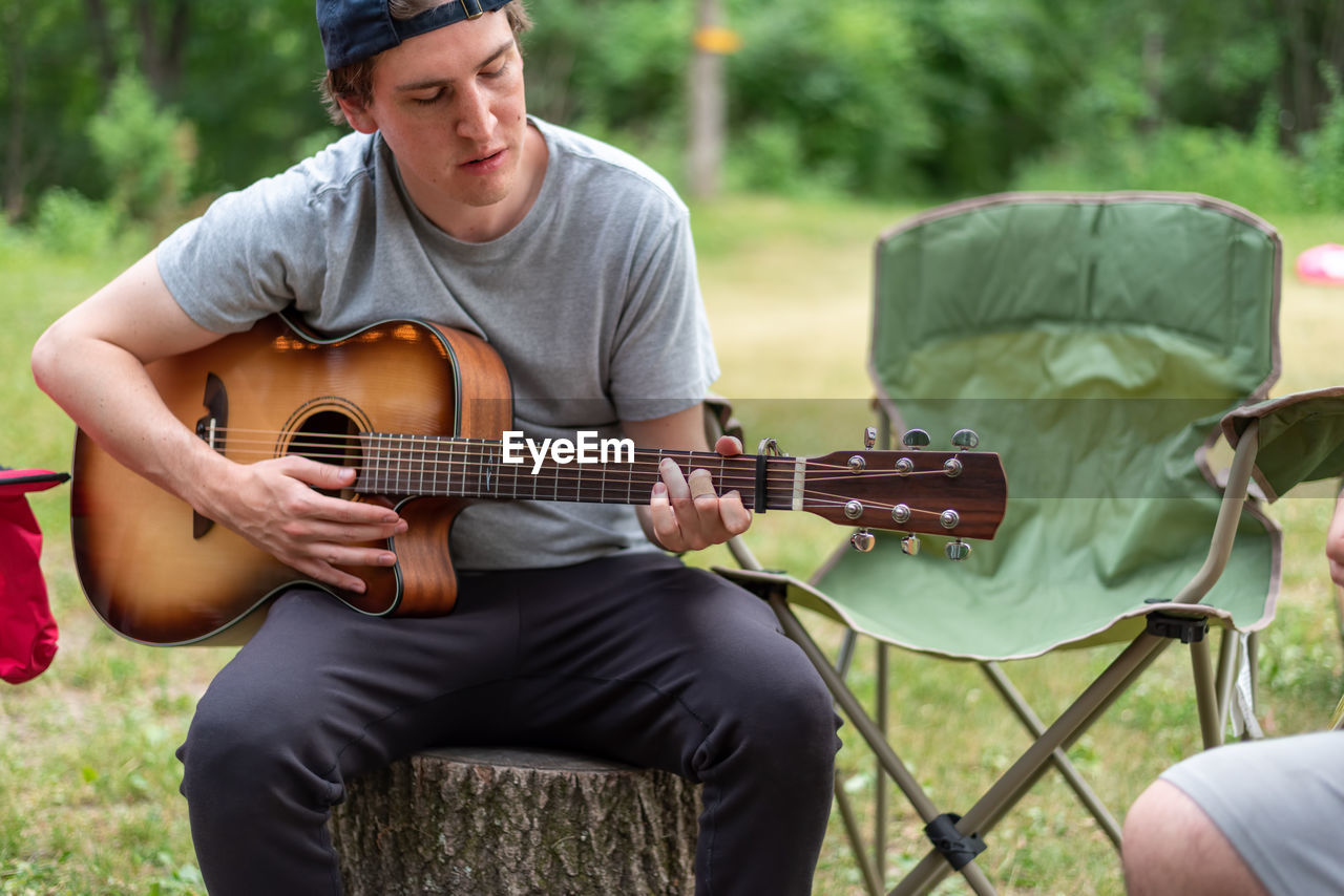 Casual young man playing guitar at a campsite in summer