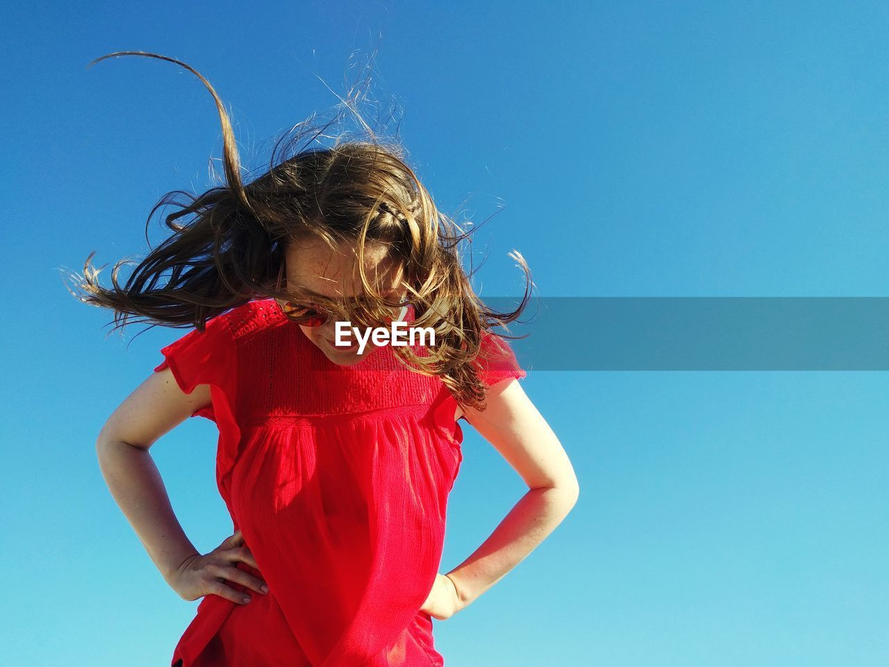 Low Angle View Of Girl Standing Against Clear Blue Sky