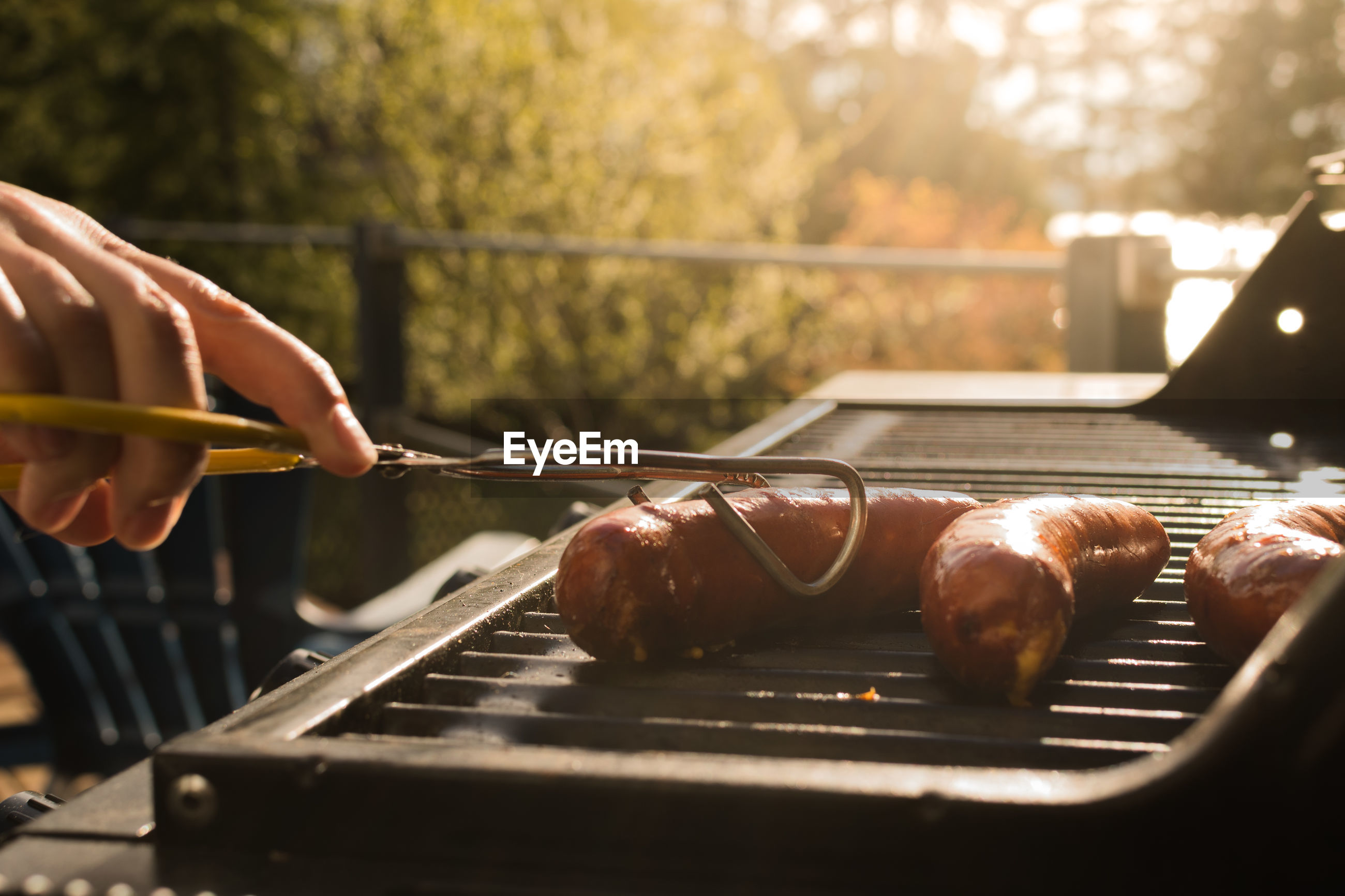 Close-up of hand grilling sausages