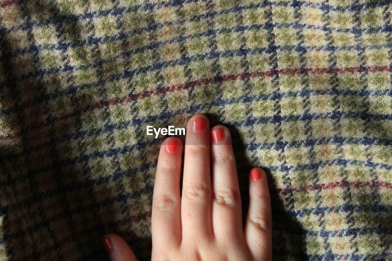 Cropped Woman Hand With Orange Nail Polish On Fabric