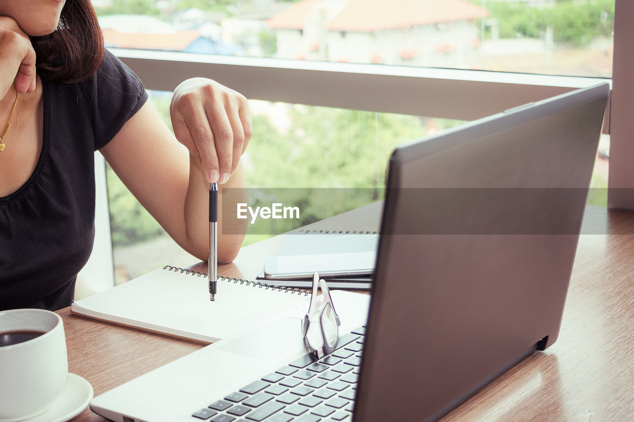 Midsection Of Woman Using Technologies At Table