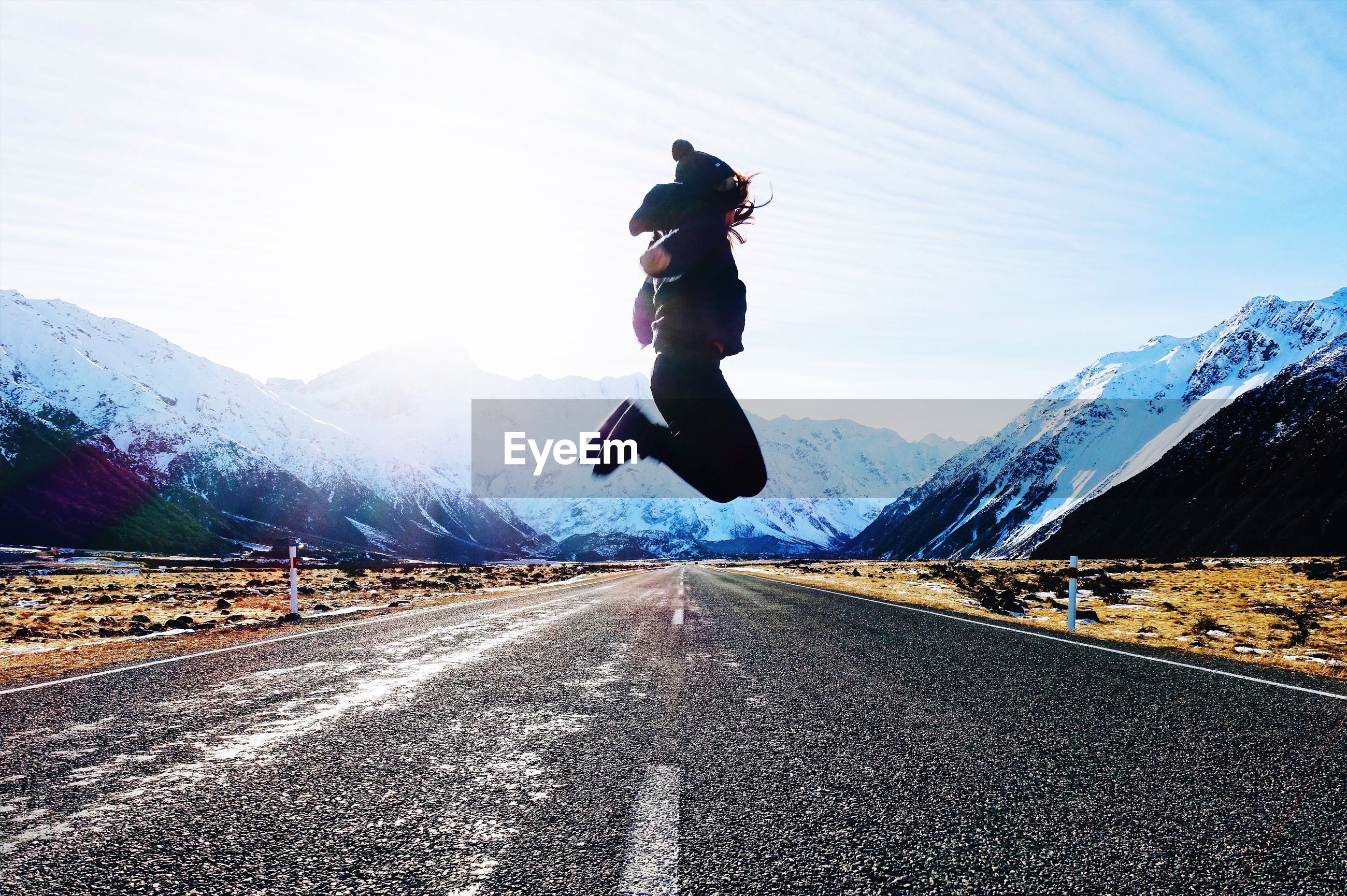 Woman jumping on road against mountain during winter