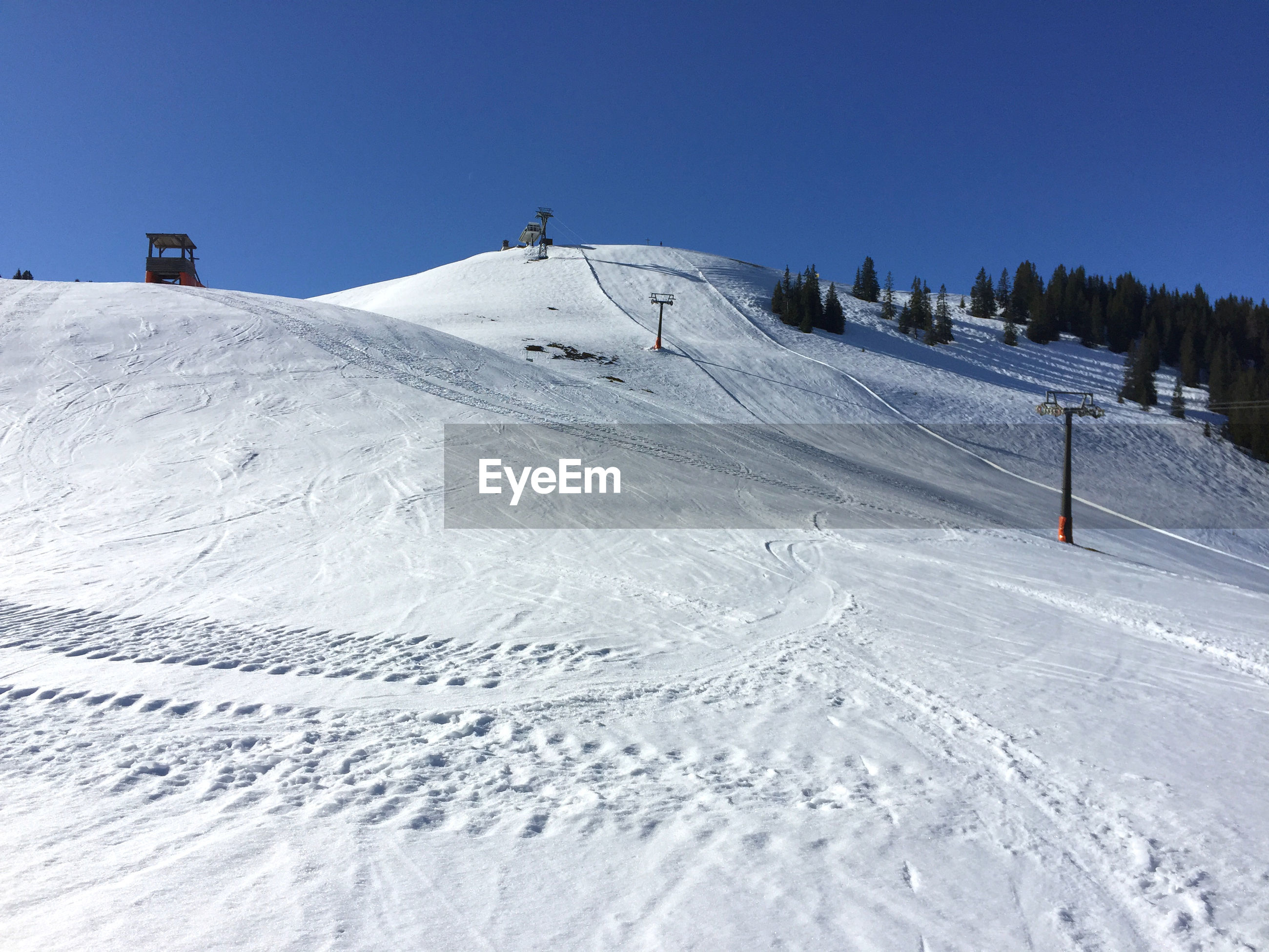 Snow covered skiing resort against clear blue sky