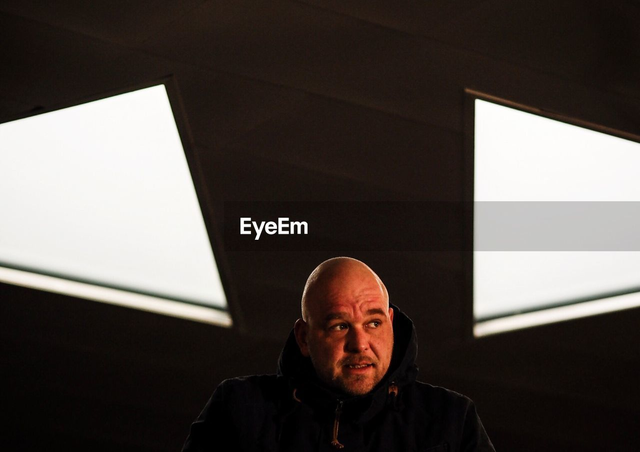 Man Against Illuminated Ceiling