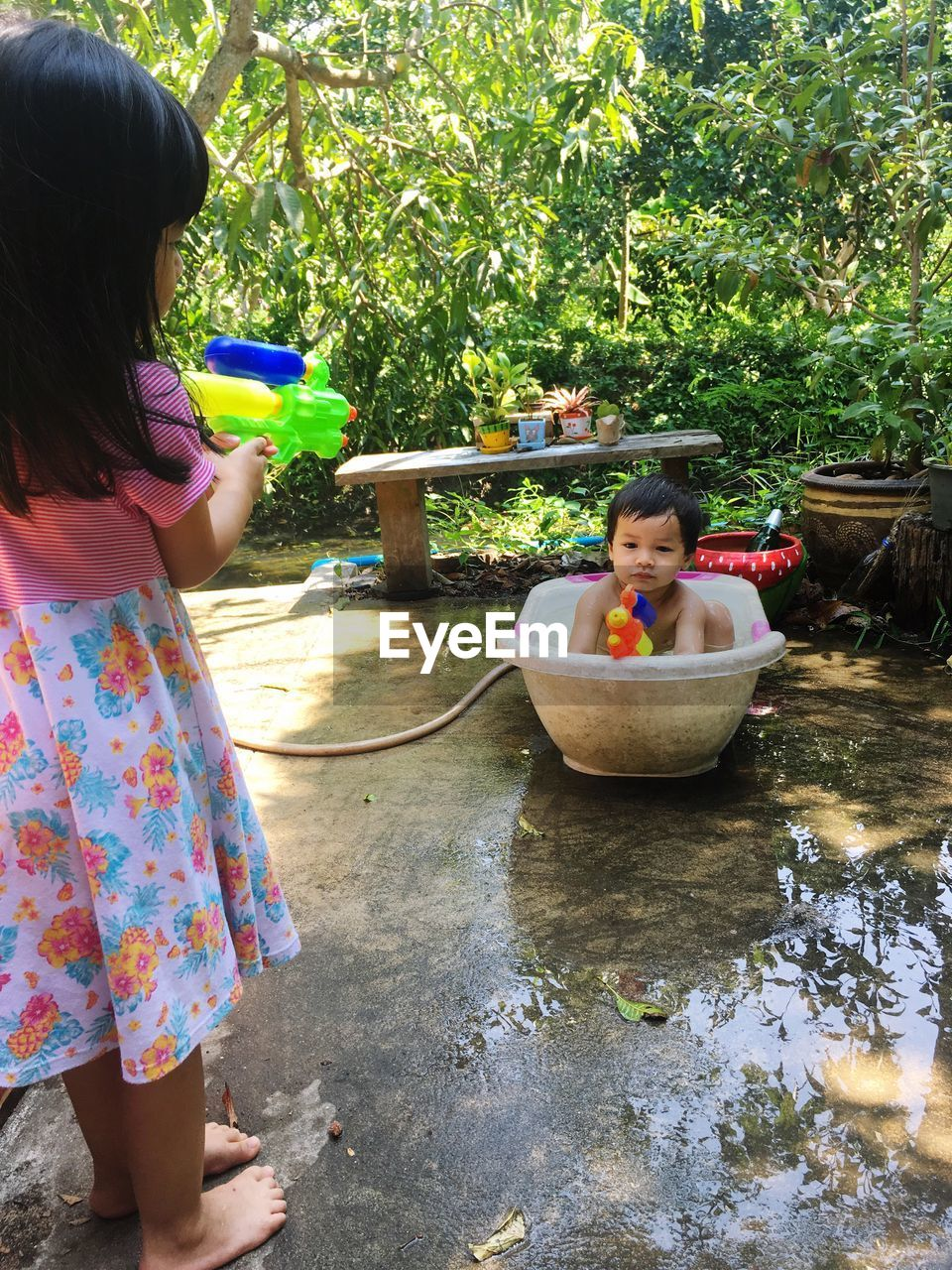 Siblings playing with squirt gun in yard