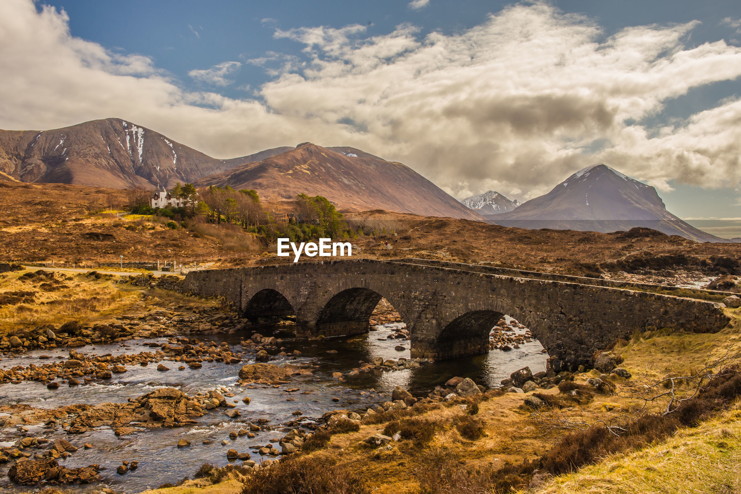 Arch bridge over river by mountains against sky