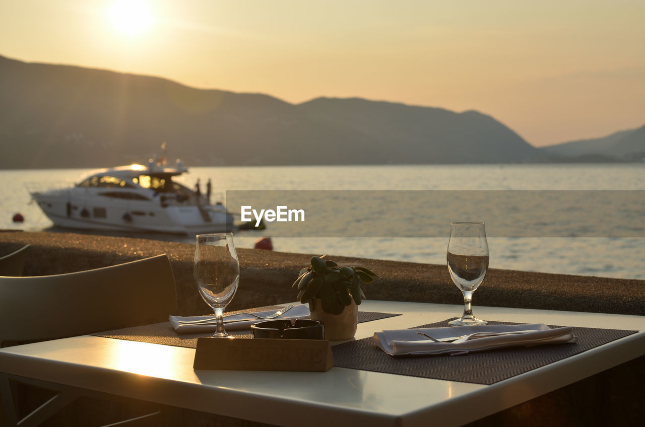 VIEW OF DRINK ON TABLE AT SUNSET
