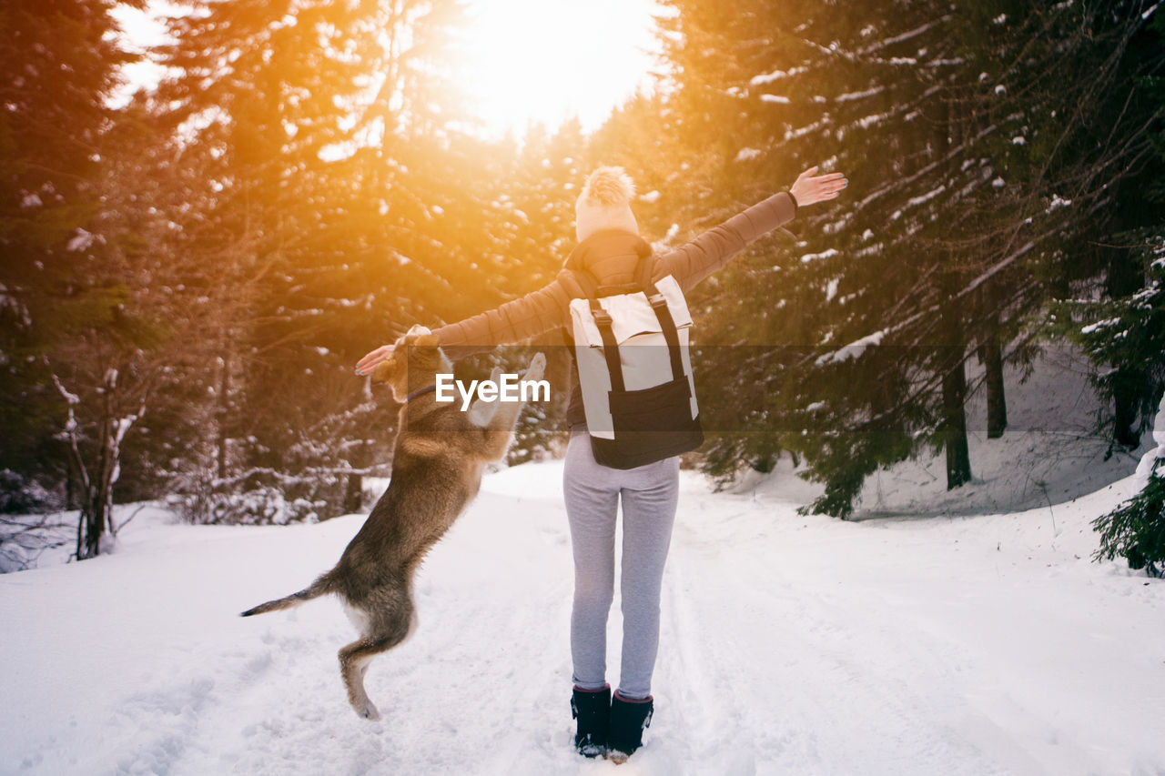 Dog Playing With Woman On Snow Covered Field During Sunrise