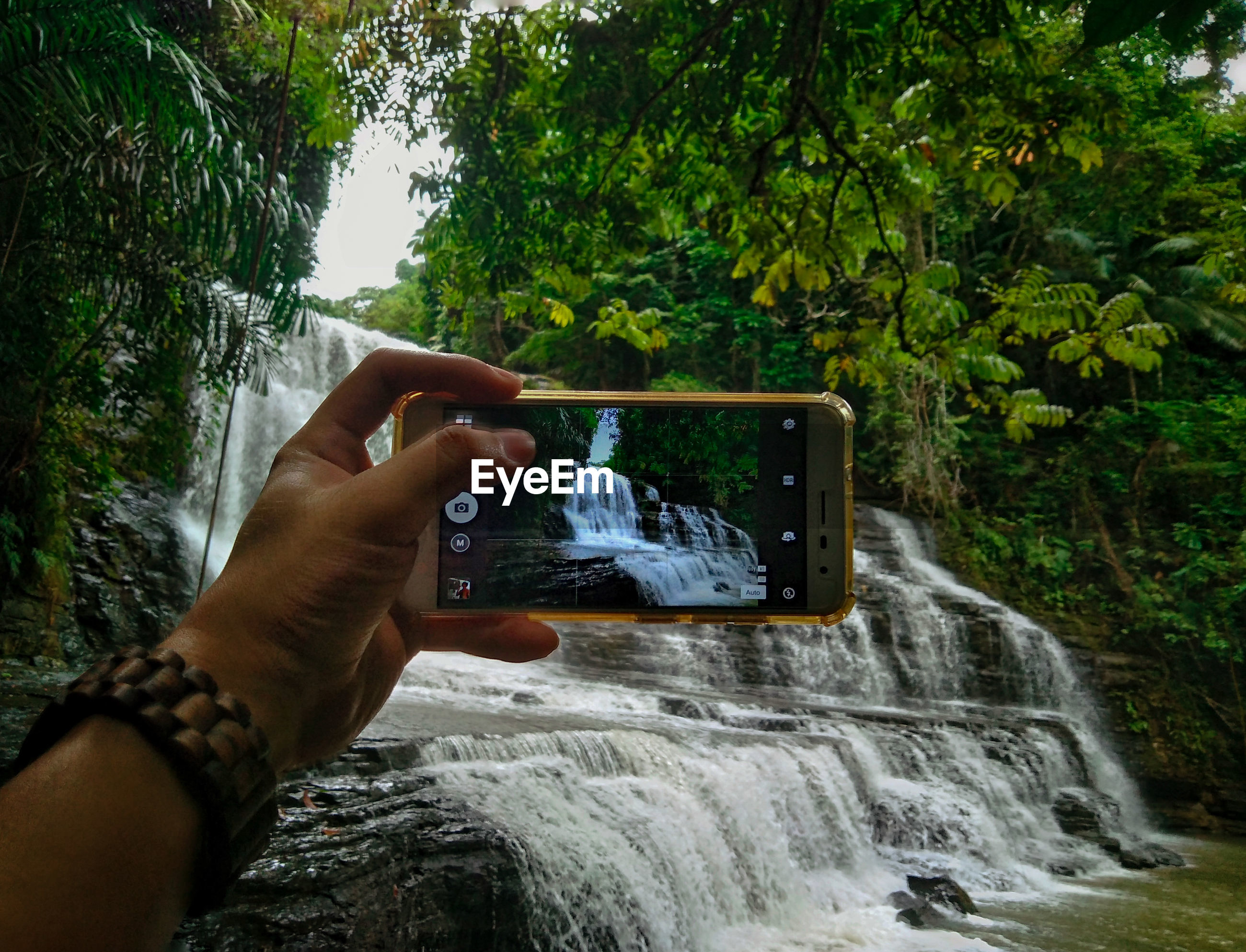 Cropped image of hand photographing waterfall through mobile phone