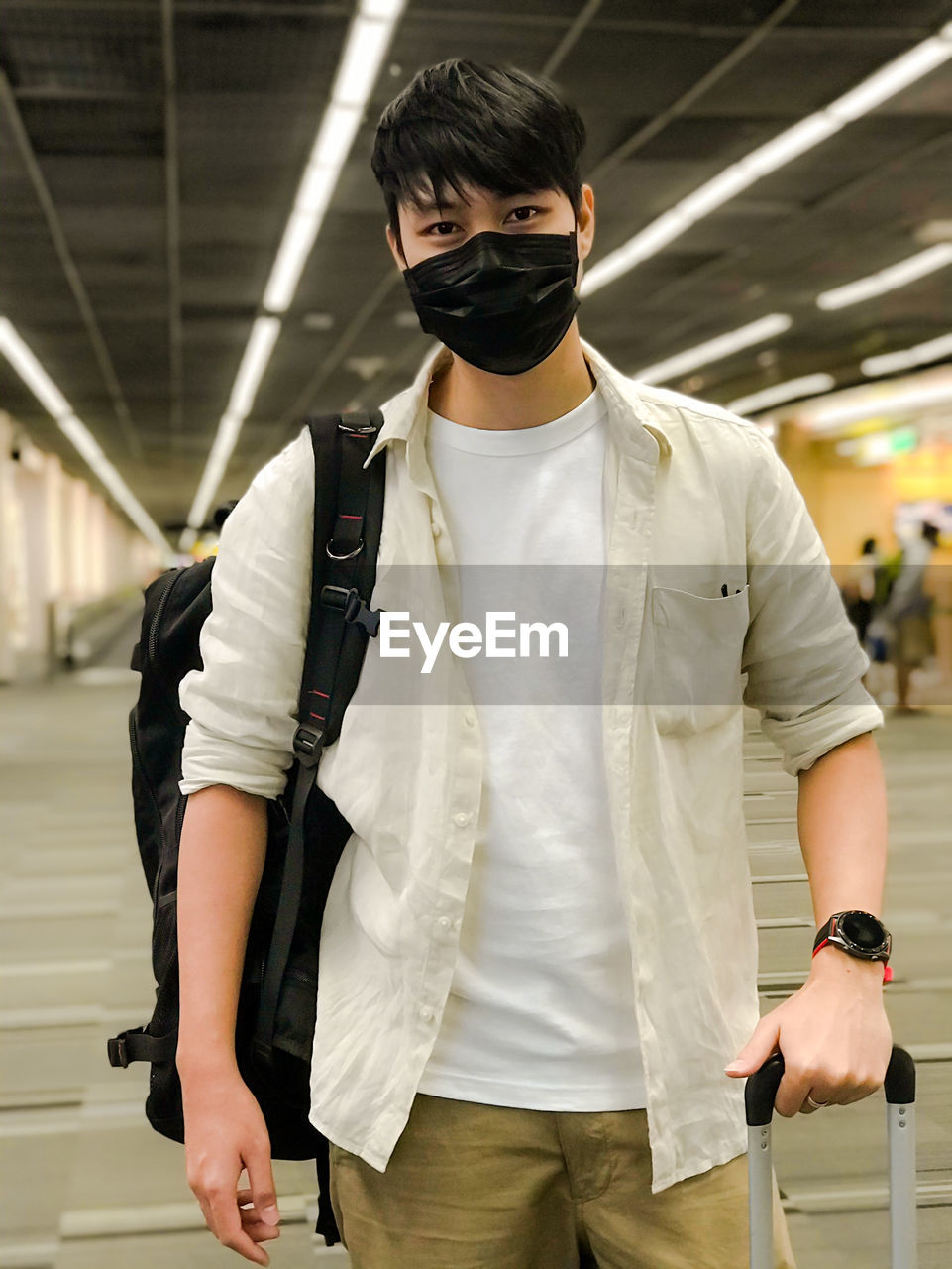 Portrait of young man wearing mask standing at airport