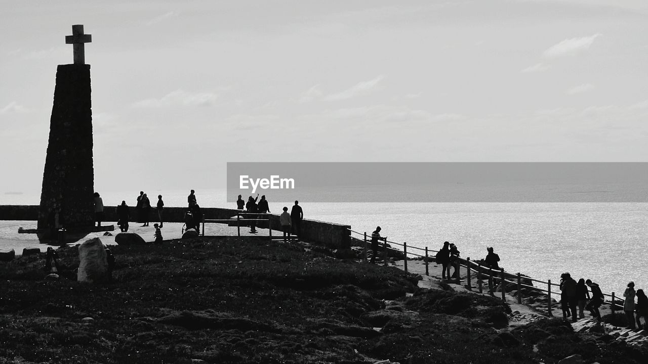 Silhouette People Visiting Cross At Sea Shore Against Sky