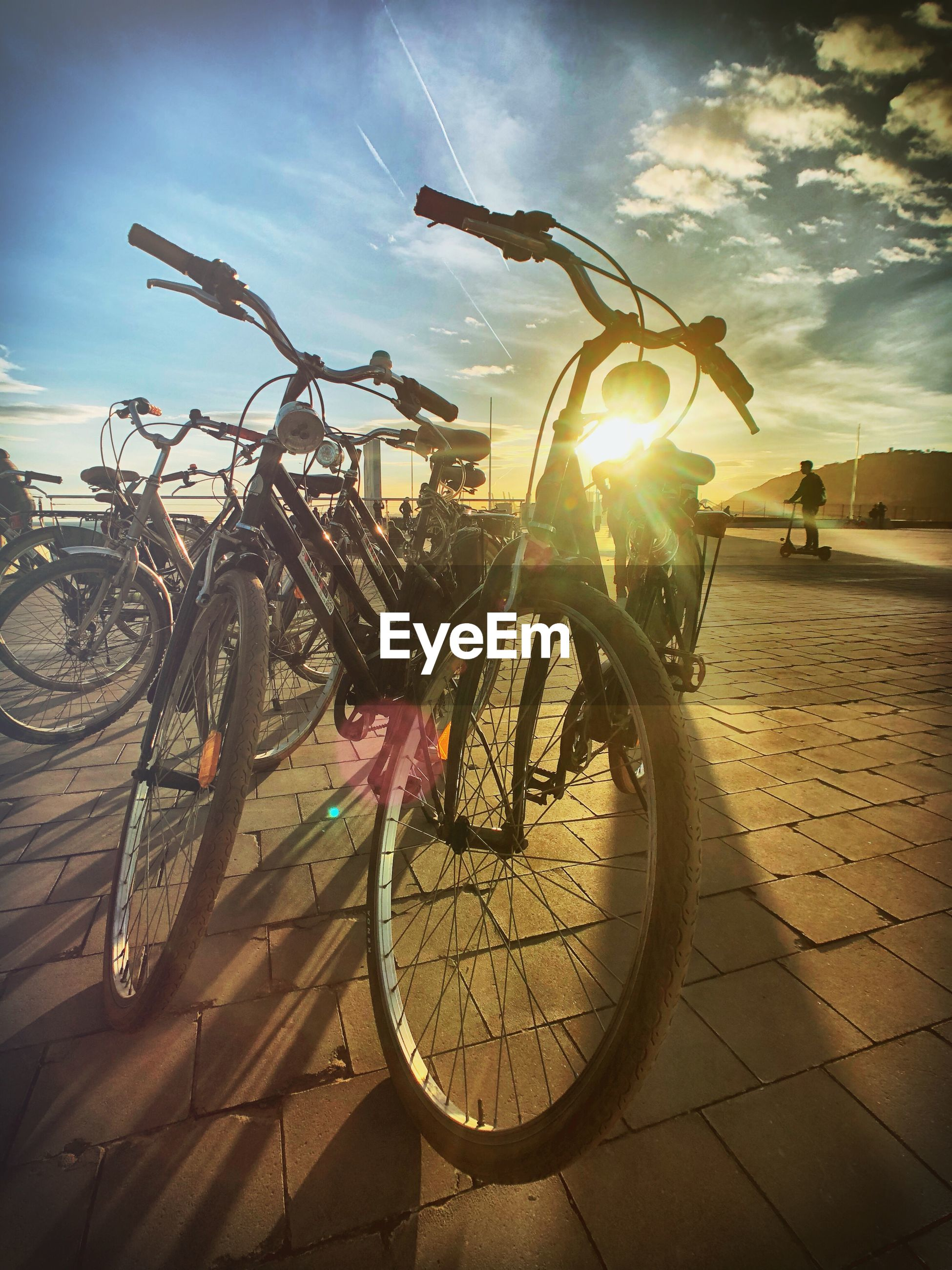 Bicycles parked on footpath against sky during sunset