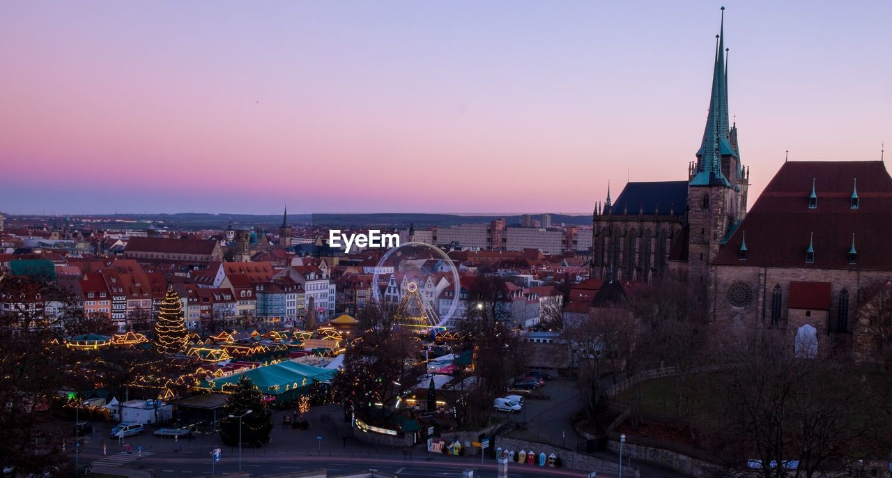 architecture, building exterior, built structure, city, sunset, outdoors, city life, high angle view, town, cityscape, large group of people, sky, illuminated, clear sky, tree, crowd, day, people