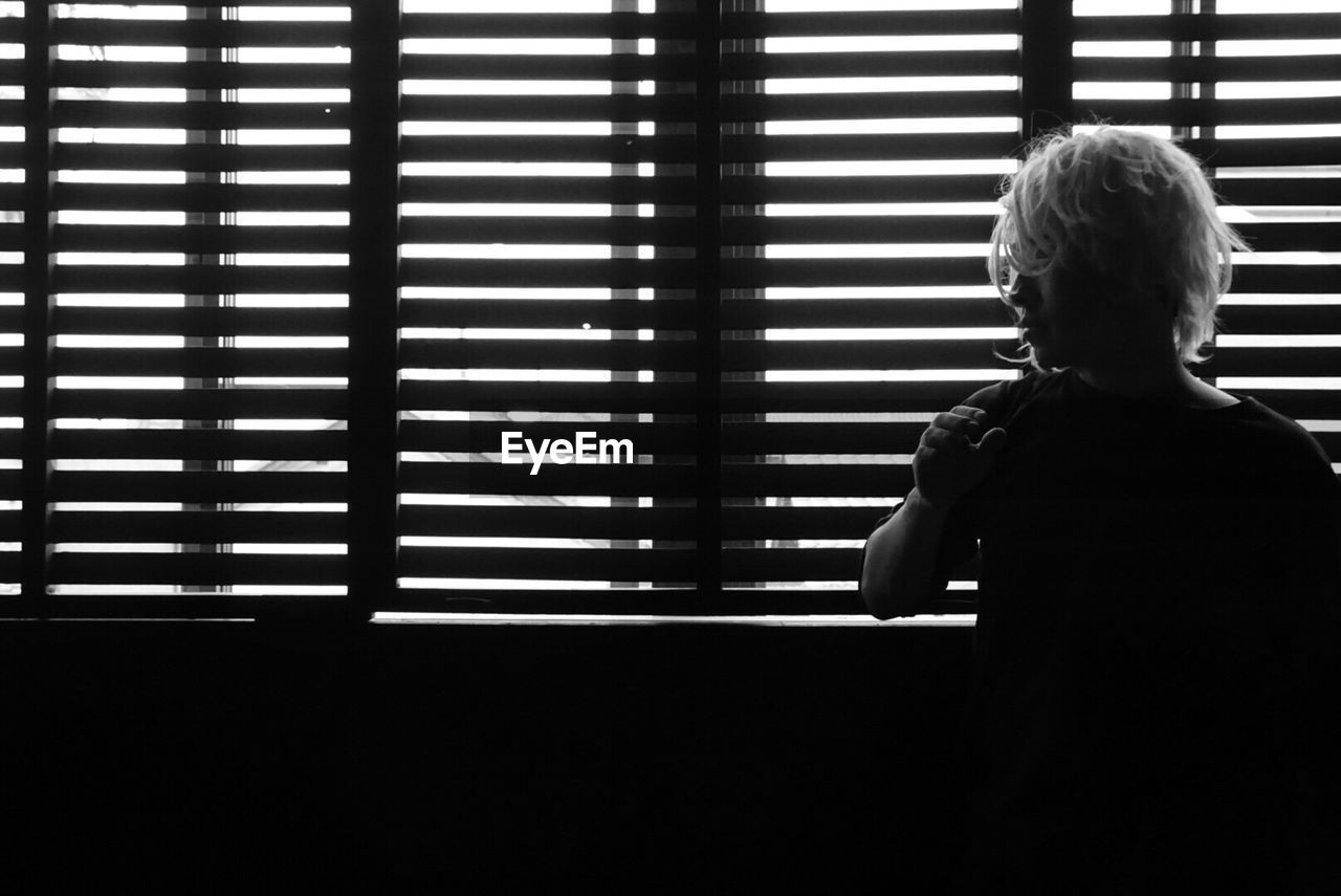 real people, child, one person, indoors, leisure activity, lifestyles, window, childhood, males, rear view, men, boys, blinds, home interior, waist up, standing, pattern, day, looking, innocence