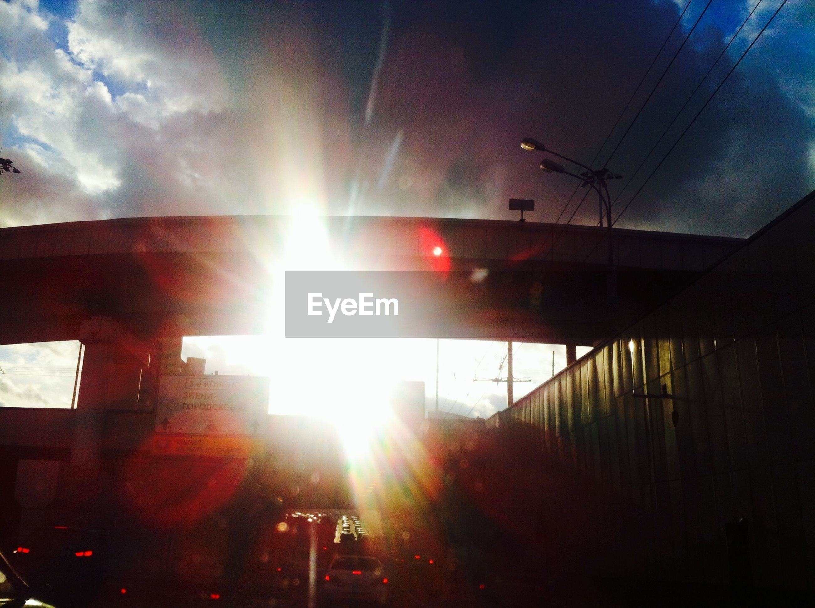 sun, sunbeam, lens flare, sunlight, transportation, built structure, sky, architecture, mode of transport, land vehicle, car, building exterior, bright, sunny, sunset, low angle view, cloud - sky, street, outdoors, day