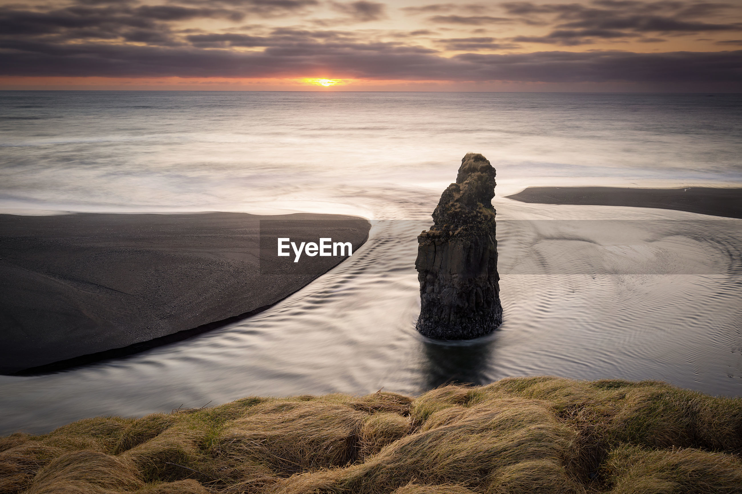 Scenic view of sea with rock formation against sky during sunset