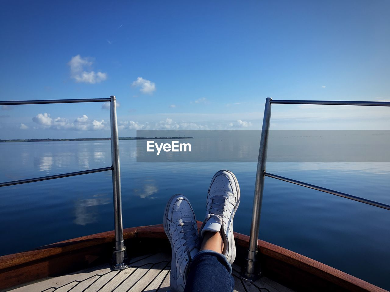 Low Section Of Woman Resting On Boat By Sea Against Sky