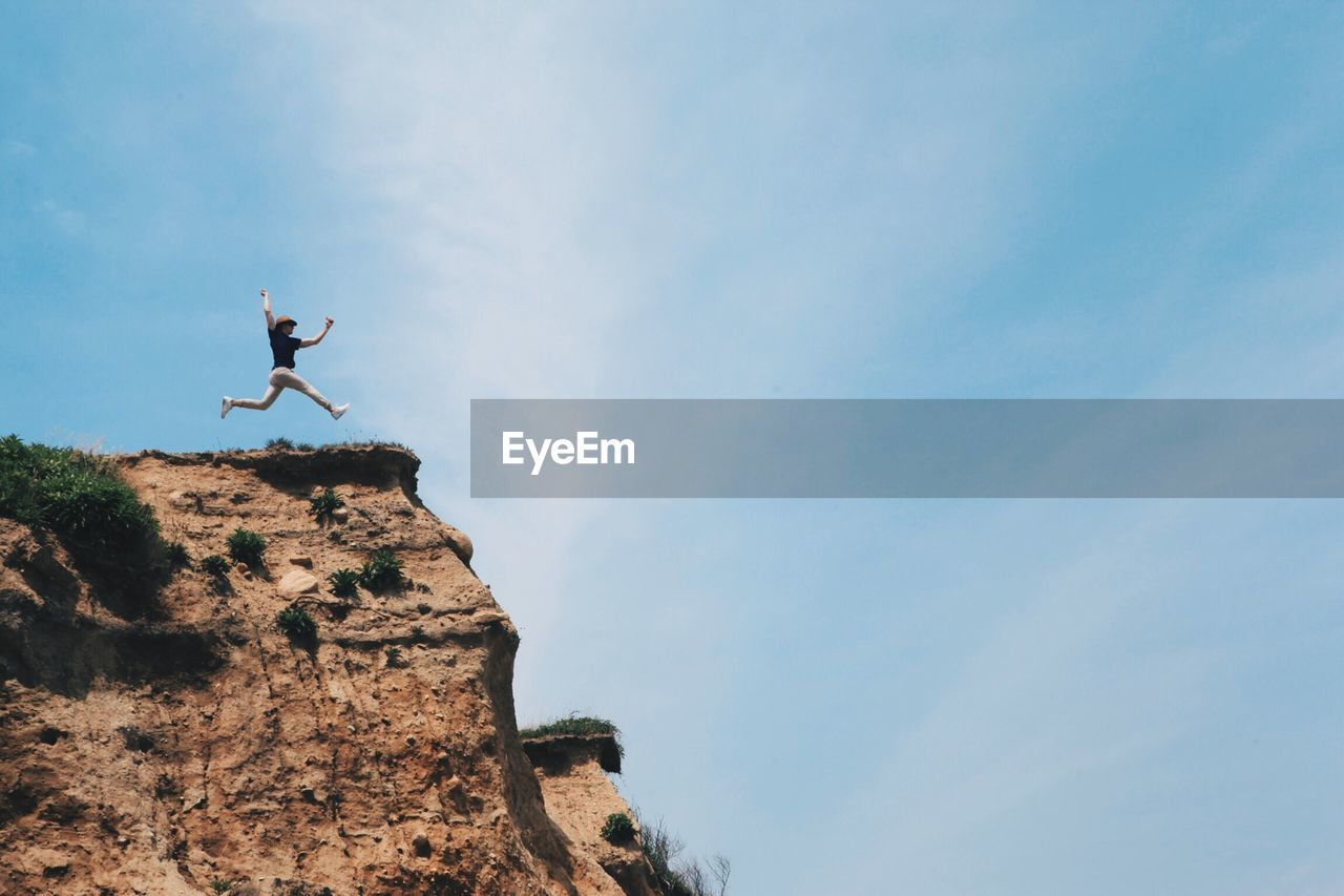 Low Angle View Of Person Jumping On Cliff Against Cloudy Sky