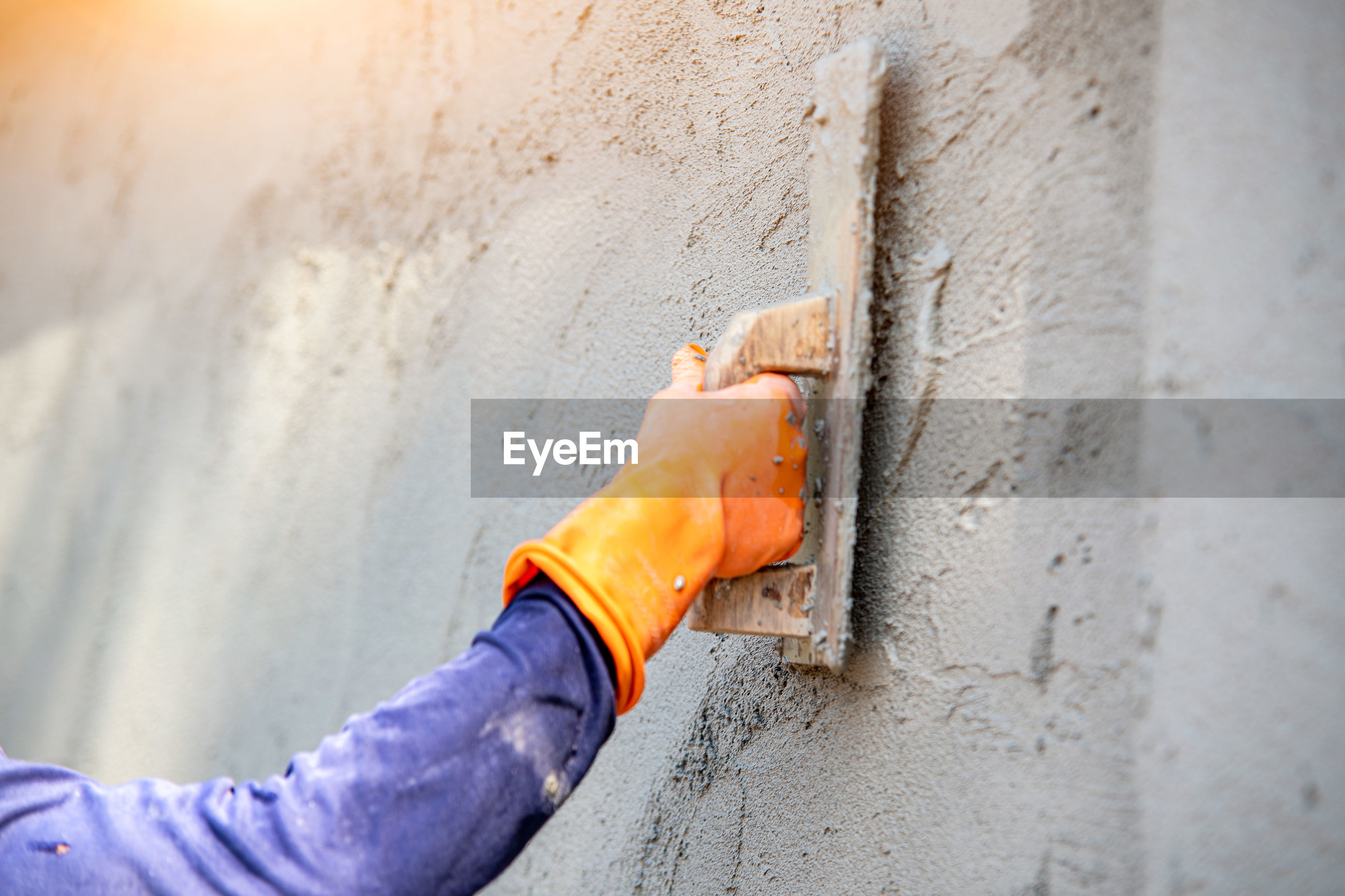 CLOSE-UP OF HANDS WORKING ON CONCRETE WALL