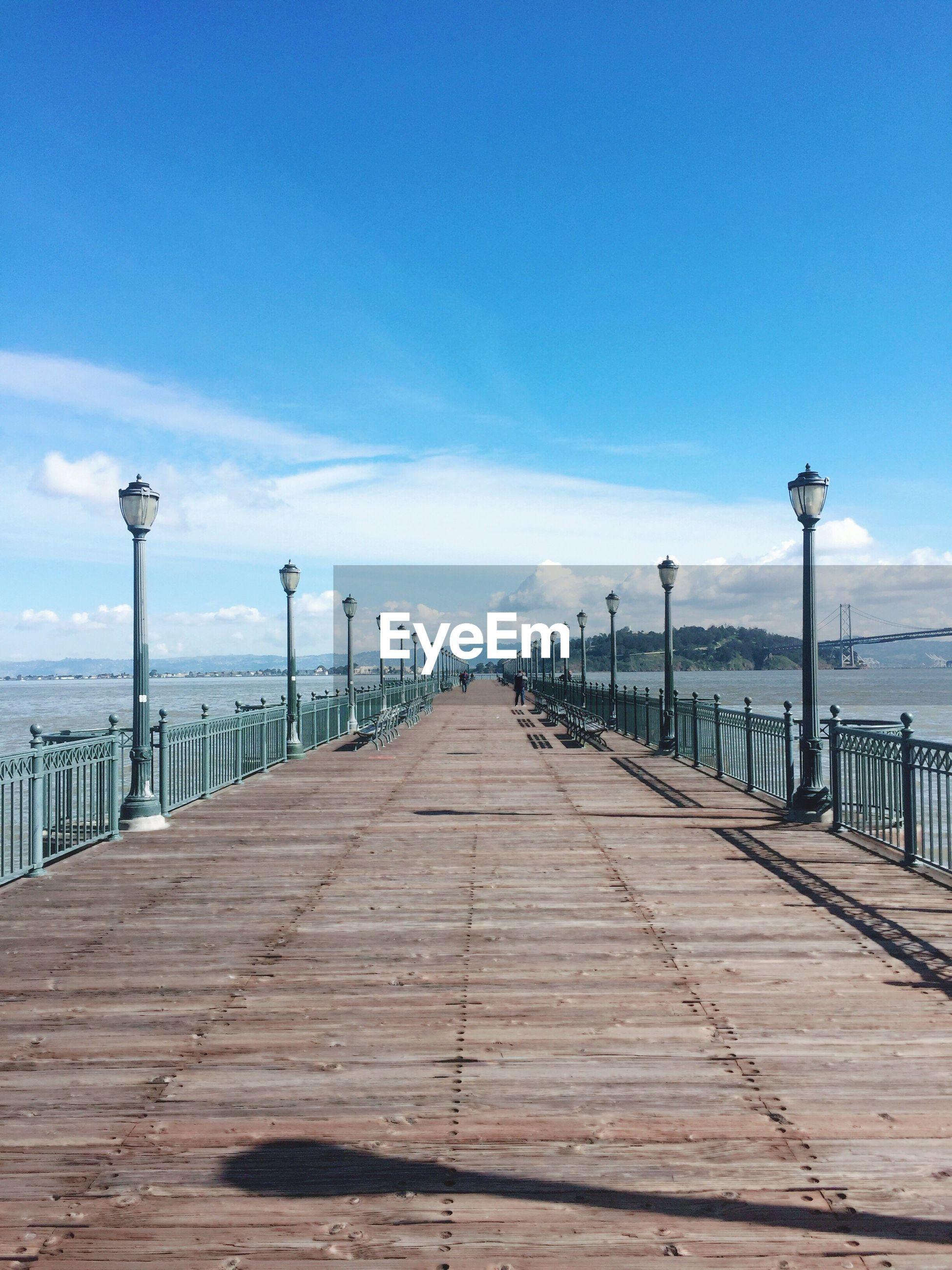 Pier leading towards sea against blue sky