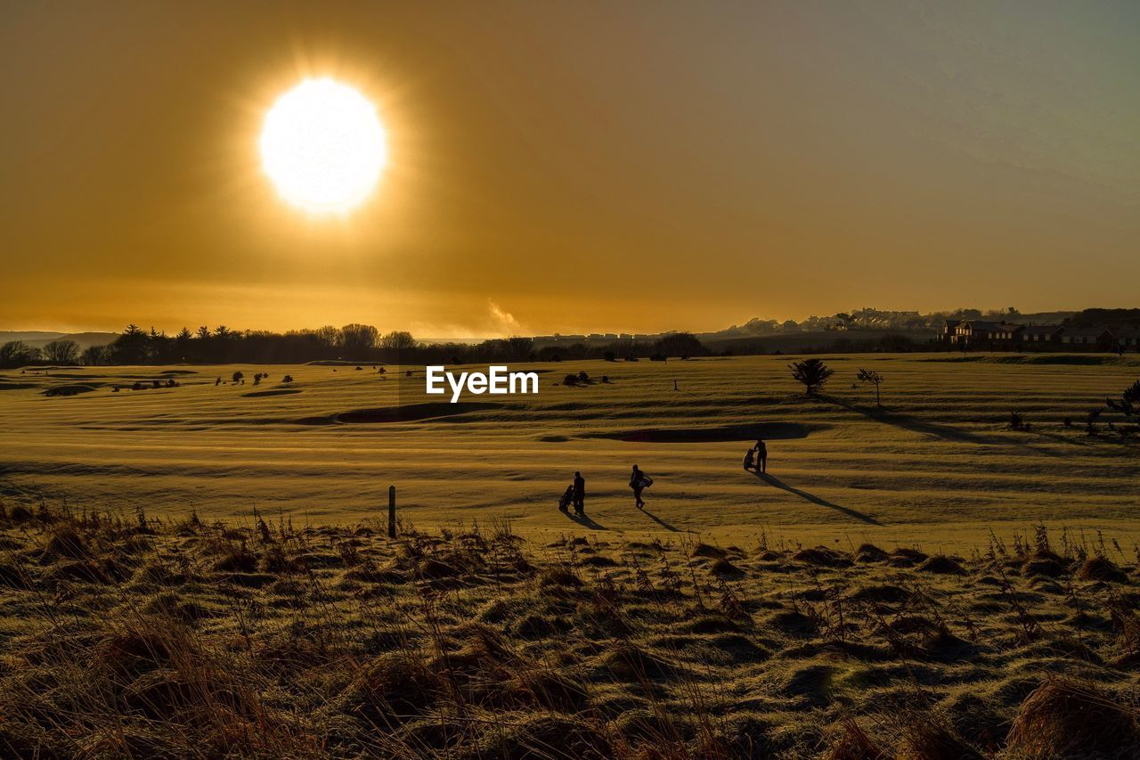 High Angle View Of People Walking On Golf Course During Sunset
