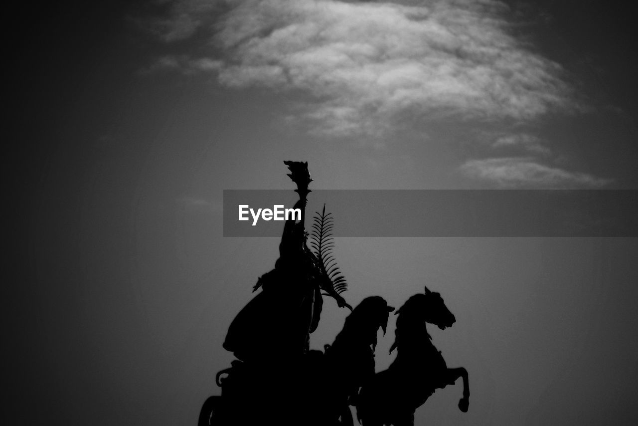 sky, cloud - sky, silhouette, real people, art and craft, sculpture, human representation, representation, statue, people, men, nature, creativity, two people, low angle view, riding, male likeness, ride, lifestyles