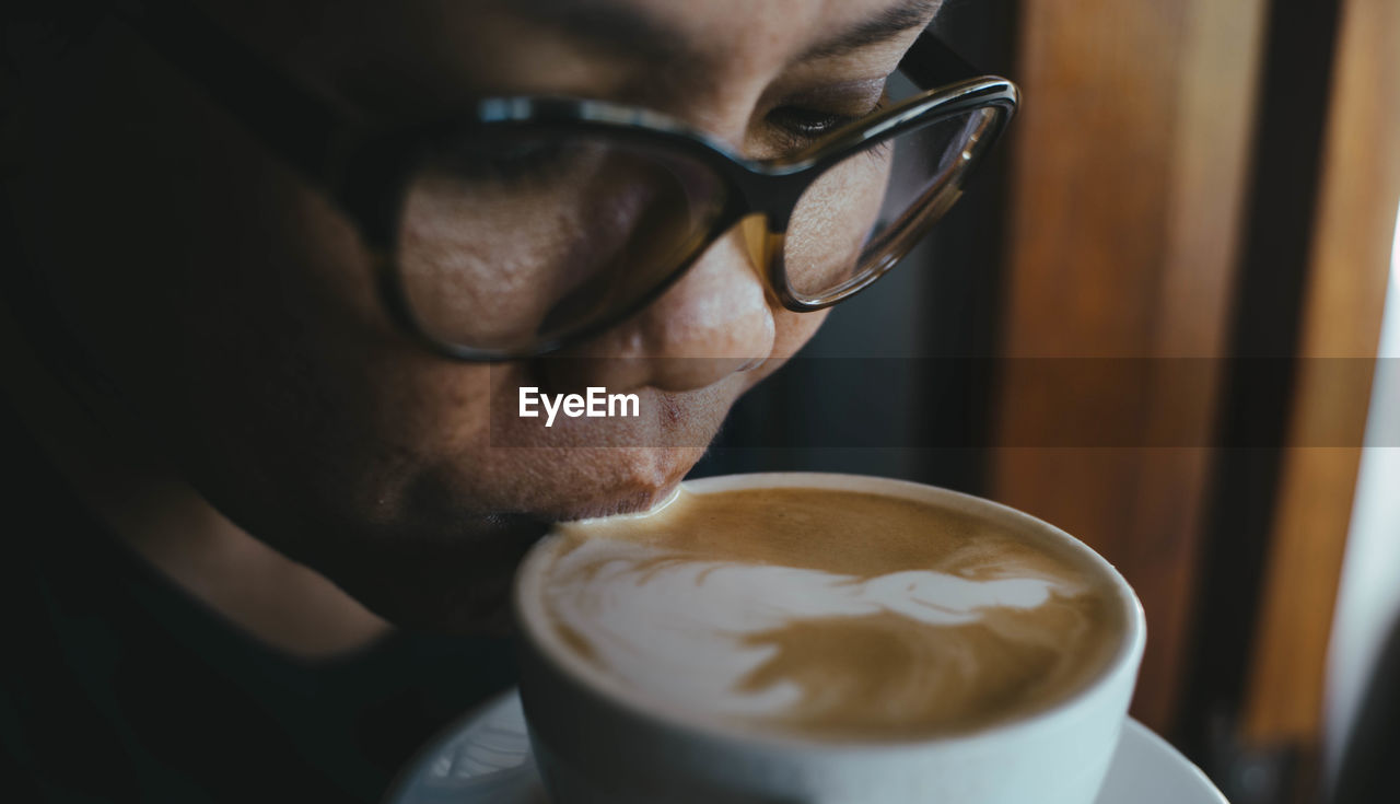 Close-Up Of Woman Drinking Coffee From Cup In Cafe
