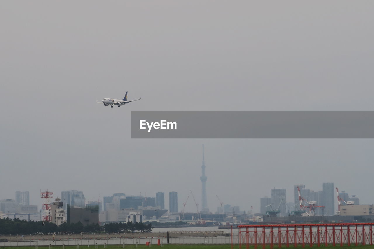 Airplane flying over buildings in city against sky