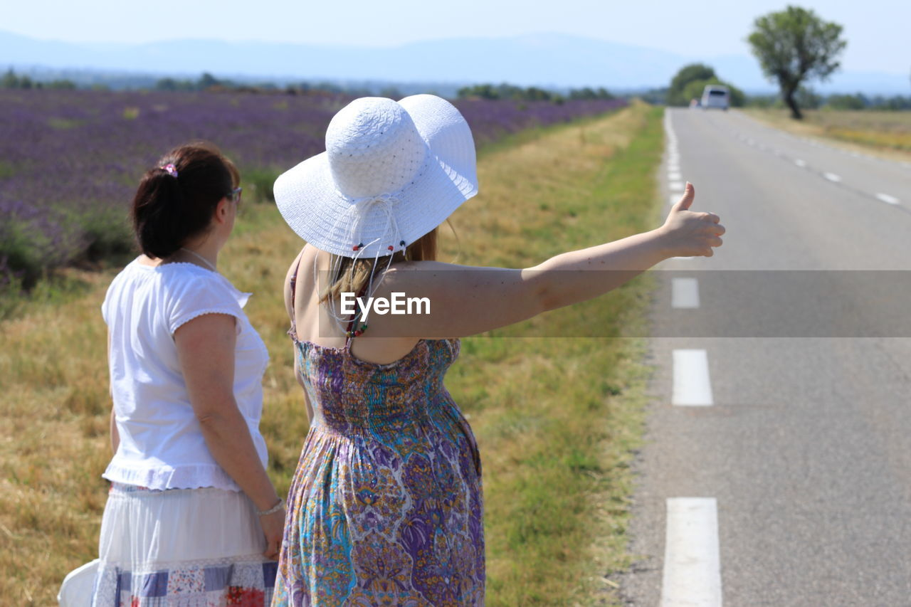 women, rear view, real people, road, focus on foreground, leisure activity, adult, nature, lifestyles, day, casual clothing, three quarter length, hat, clothing, people, transportation, standing, togetherness, two people, sunlight, outdoors, hairstyle, couple - relationship, human arm