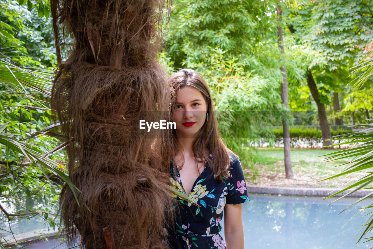 Portrait of young woman by tree trunk