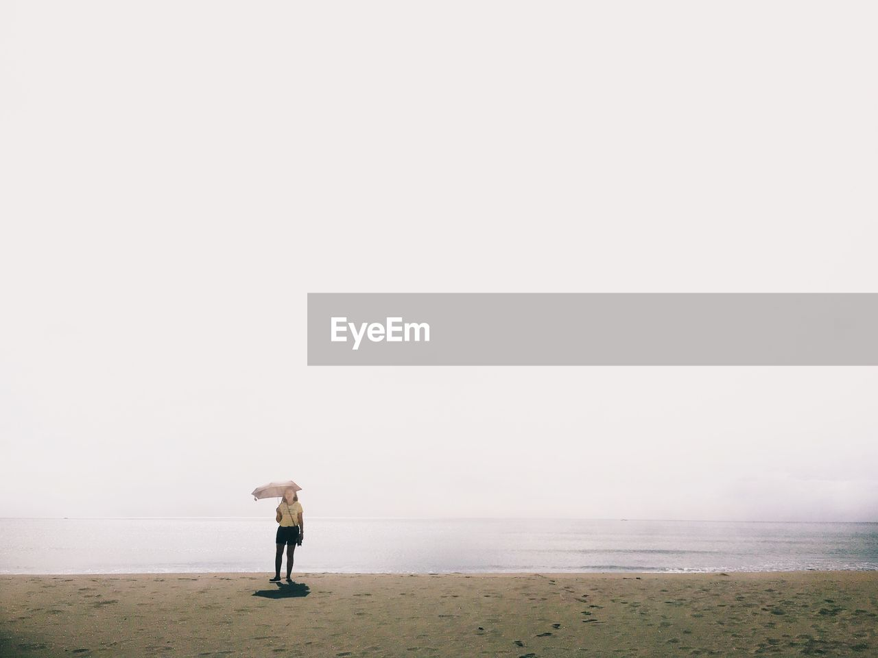 Young Woman Standing At Beach During Foggy Weather