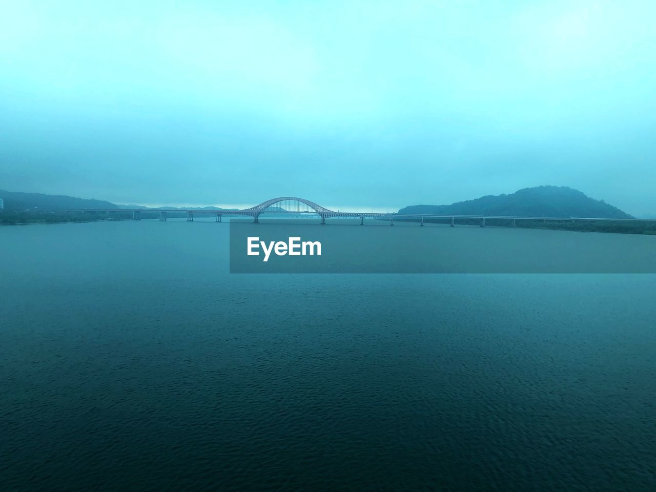 water, sea, scenics - nature, beauty in nature, waterfront, tranquil scene, tranquility, sky, nature, no people, day, mountain, connection, bridge, outdoors, non-urban scene, bridge - man made structure, idyllic, fog