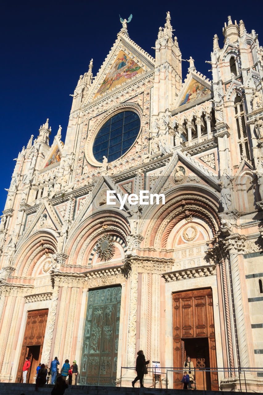 architecture, building exterior, built structure, place of worship, belief, religion, spirituality, building, group of people, arch, travel destinations, sky, incidental people, facade, crowd, travel, outdoors, gothic style