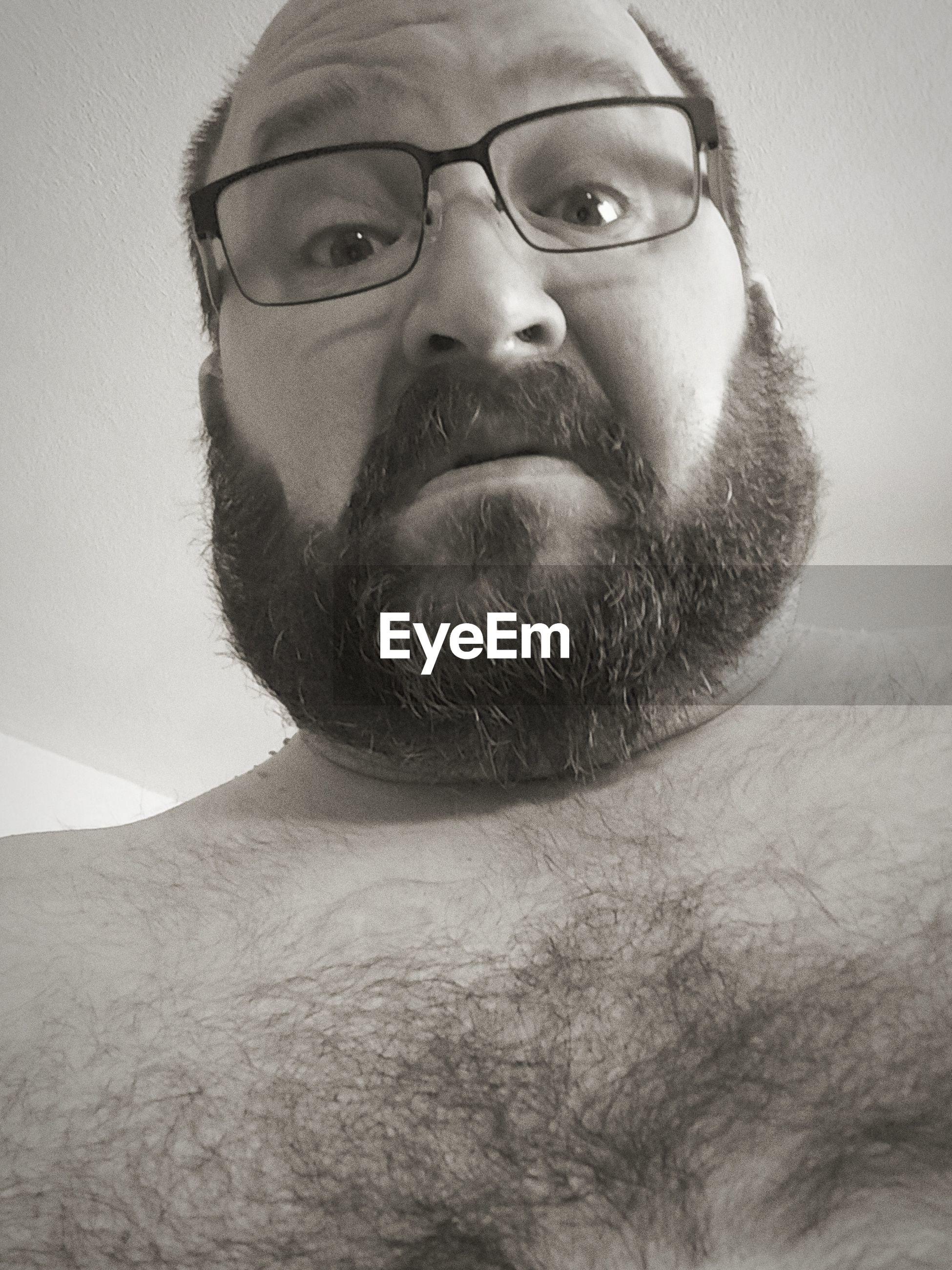 Portrait of shirtless man wearing eyeglasses