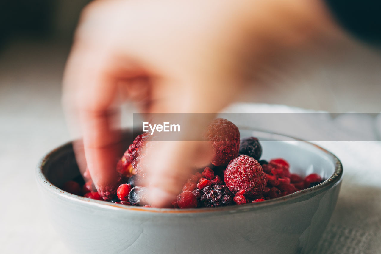 Blurred Motion Of Hand Taking Berries From Bowl