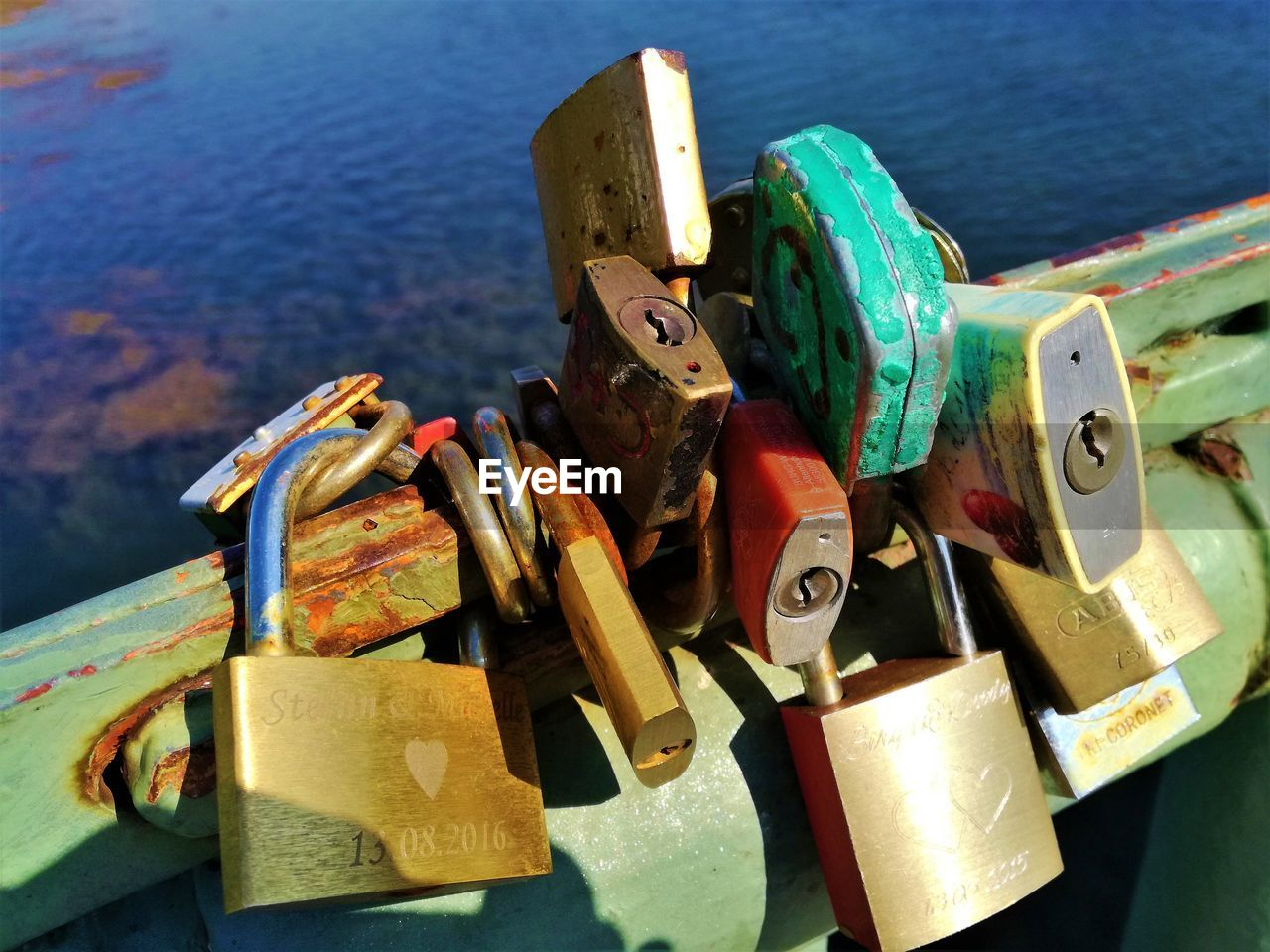 lock, metal, padlock, security, protection, water, safety, close-up, no people, variation, day, high angle view, love, love lock, river, connection, choice, nature, multi colored, outdoors