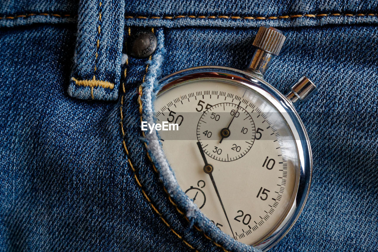 Close-up of stopwatch in jeans pocket