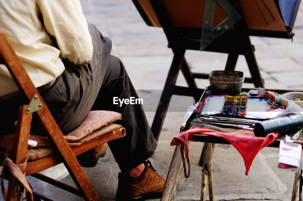 Low Section Of Man Sitting With Art And Craft Equipment On Table At Footpath