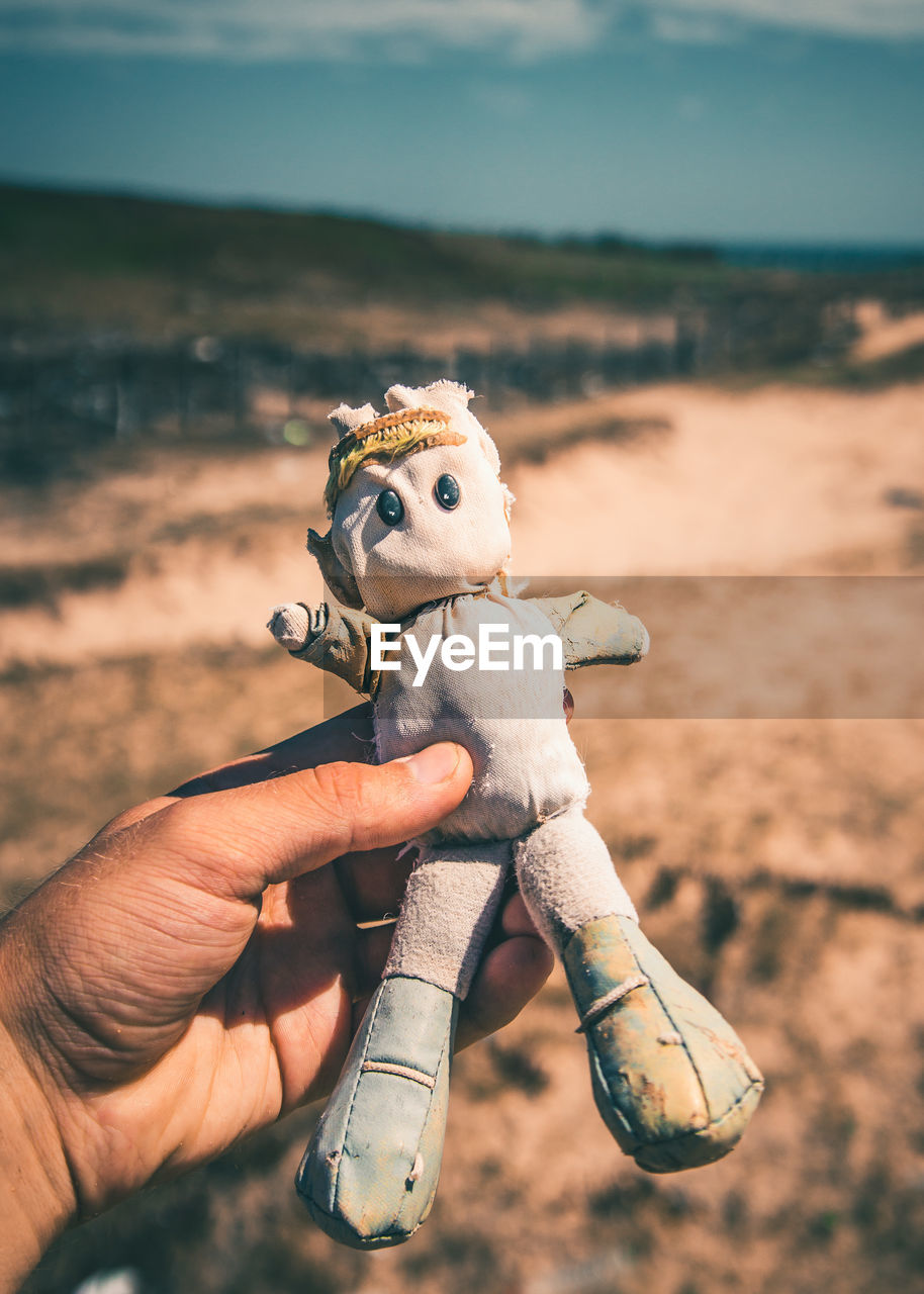 human hand, human body part, real people, one person, toy, holding, focus on foreground, men, outdoors, one animal, day, close-up, sky, nature, mammal, people