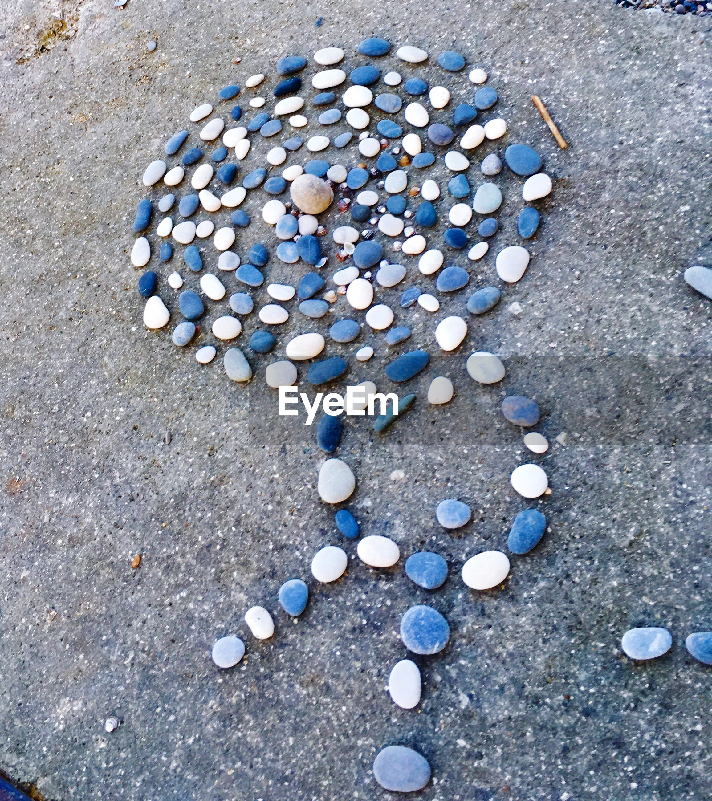 high angle view, close-up, pebble, stone - object, large group of objects, abundance, blue, repetition, shore, vibrant color, day, order, nature, arrangement, outdoors, focus on foreground, overhead view, no people, blue color, extreme close up