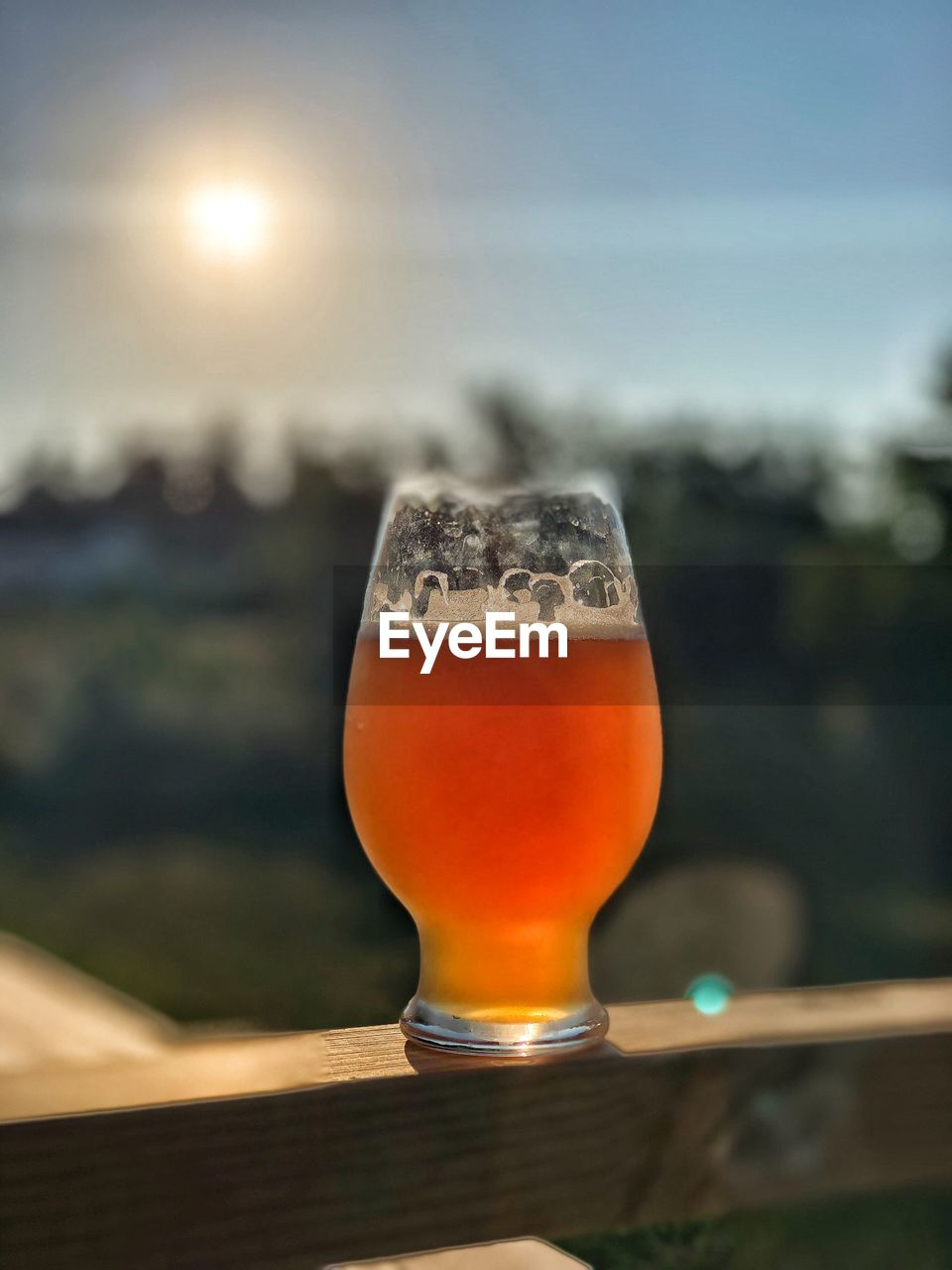 food and drink, drink, refreshment, focus on foreground, glass, alcohol, table, beer, close-up, freshness, beer - alcohol, sky, household equipment, drinking glass, glass - material, still life, sunlight, beer glass, no people, wood - material, outdoors, aperitif