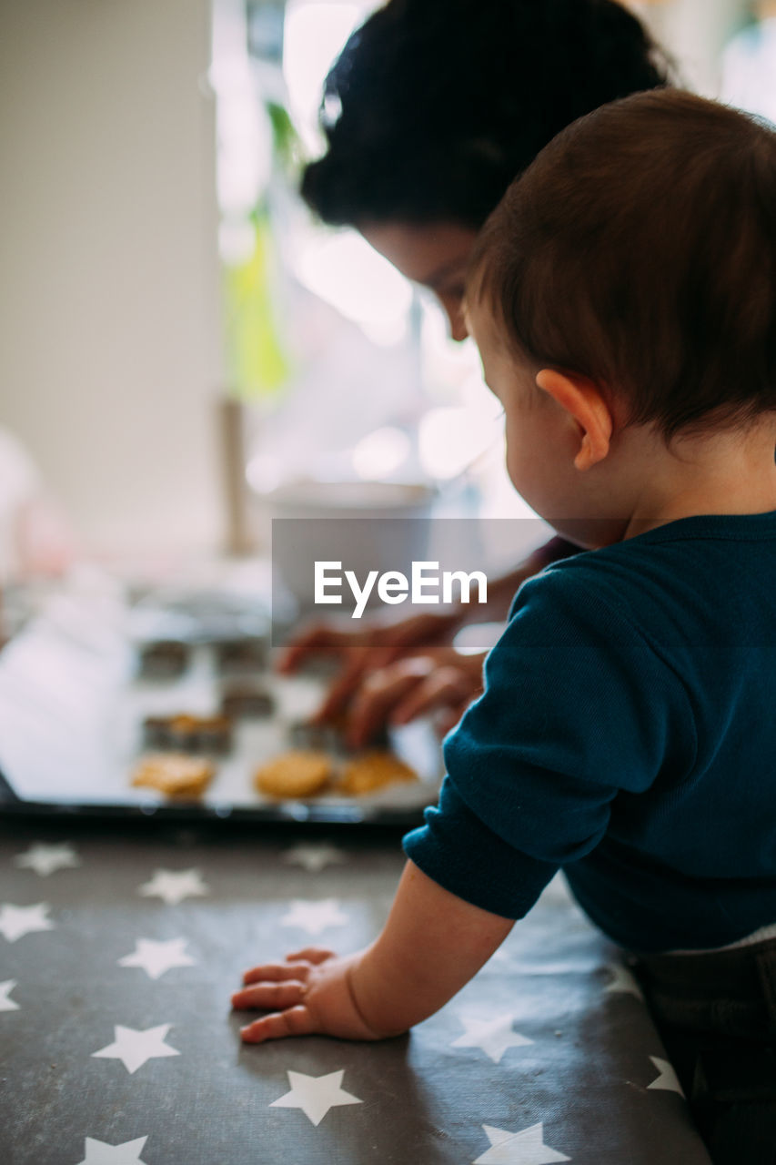 child, childhood, males, boys, men, real people, indoors, one person, focus on foreground, lifestyles, table, innocence, kitchen, home interior, home, domestic room, food and drink, looking, casual clothing, preparing food